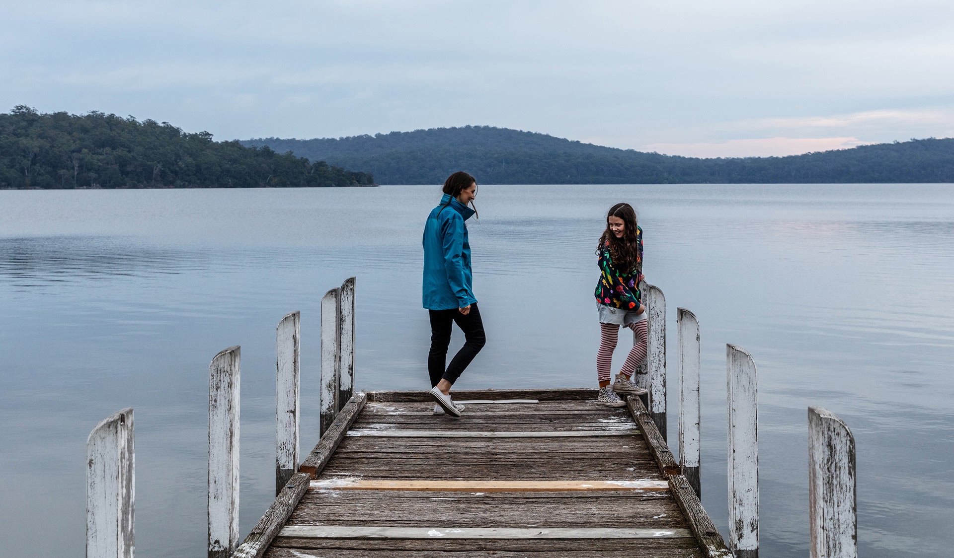 A mother and daughter linger at the end of a pier on the Mallacoota Inlet