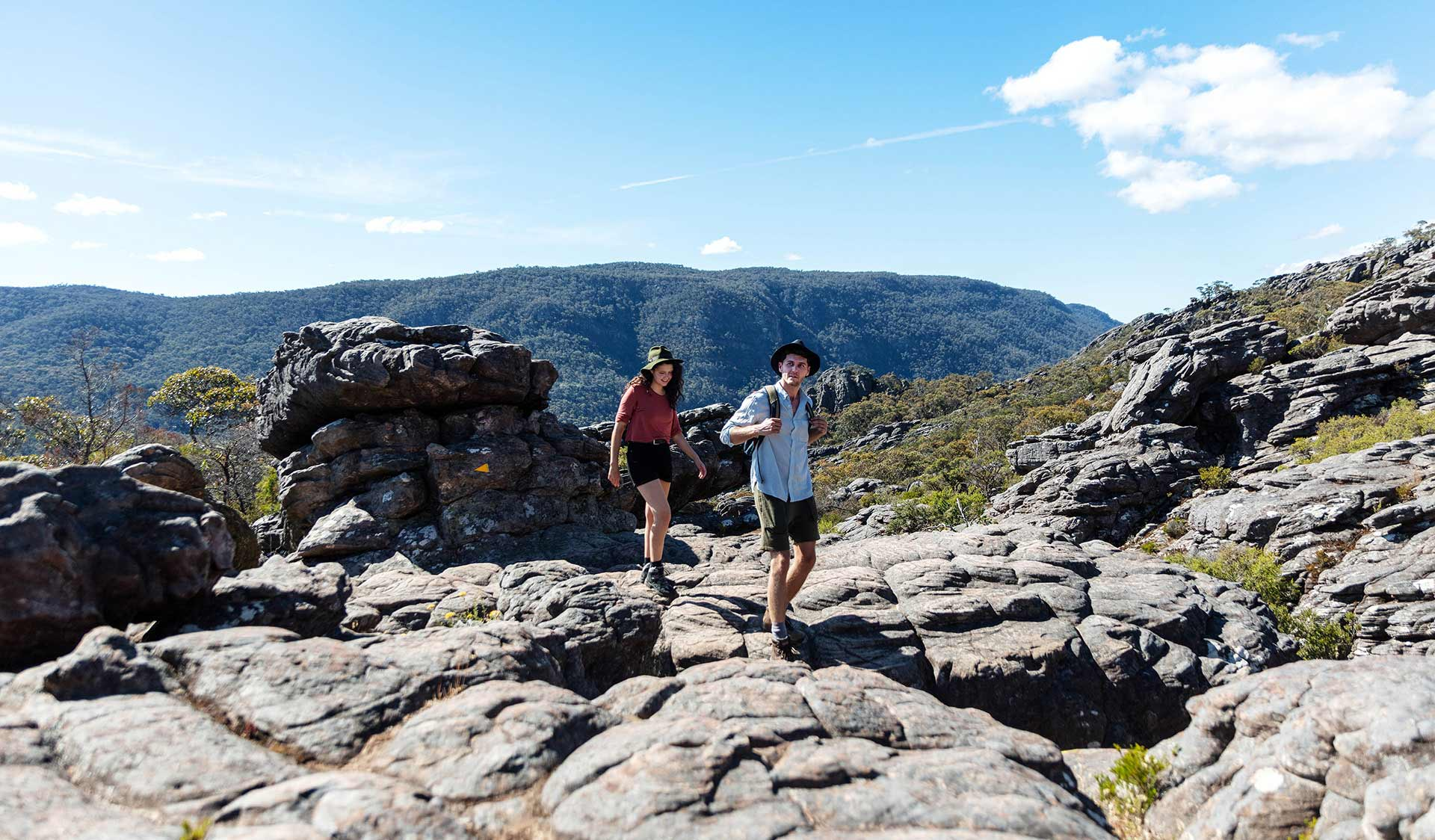 A young couple walks up through ancient lava flows to Sundial Peak in the Central Grampians.