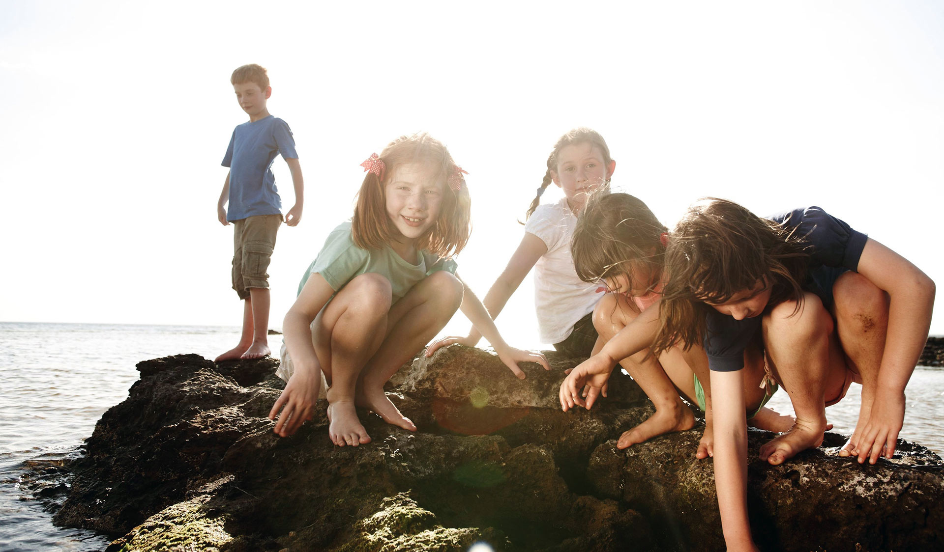 A group of five children play in the rock pools at Ricketts Point late in the afternoon.