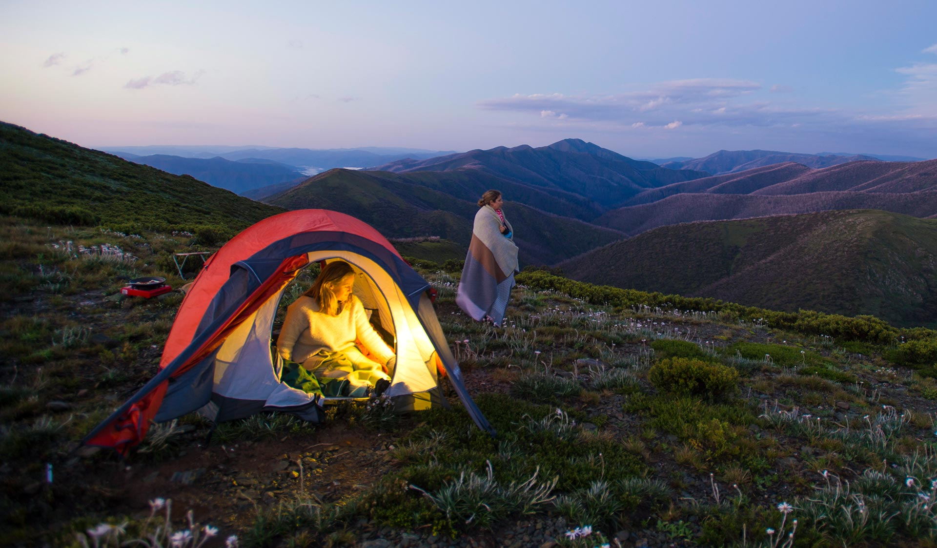 Two women camp in the Alpine National Park at twilight.