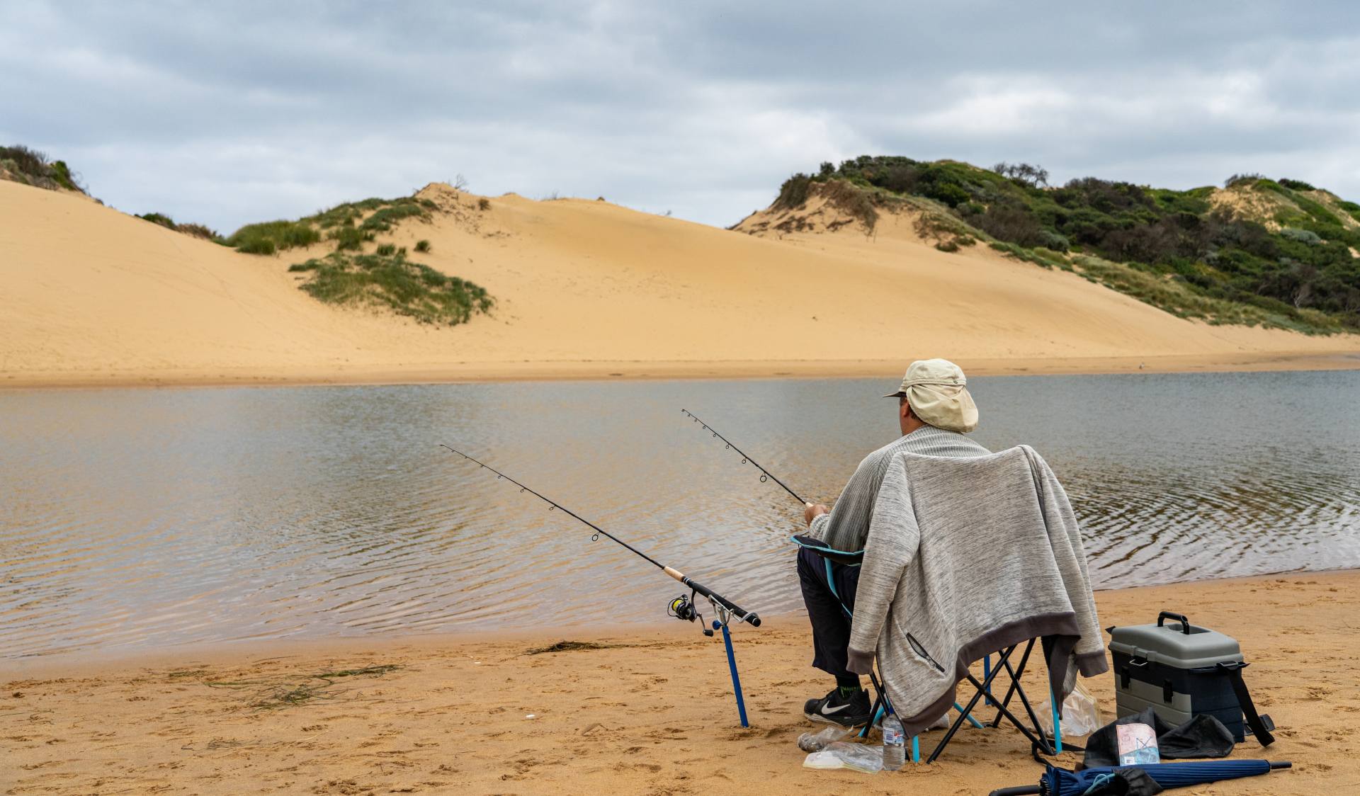 A man sits on a chair while fishing at Powlett River