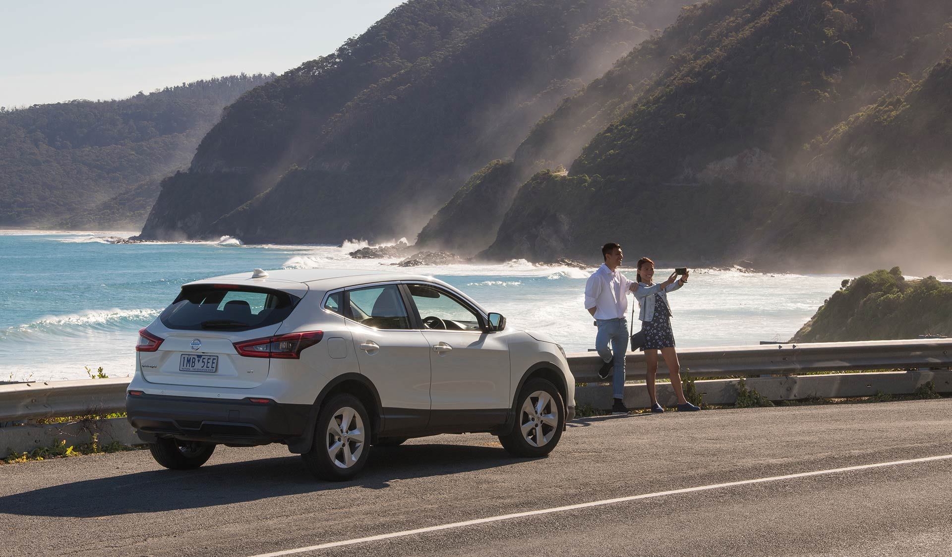 A couple stop on the side of the Great Ocean Road to take a picture.