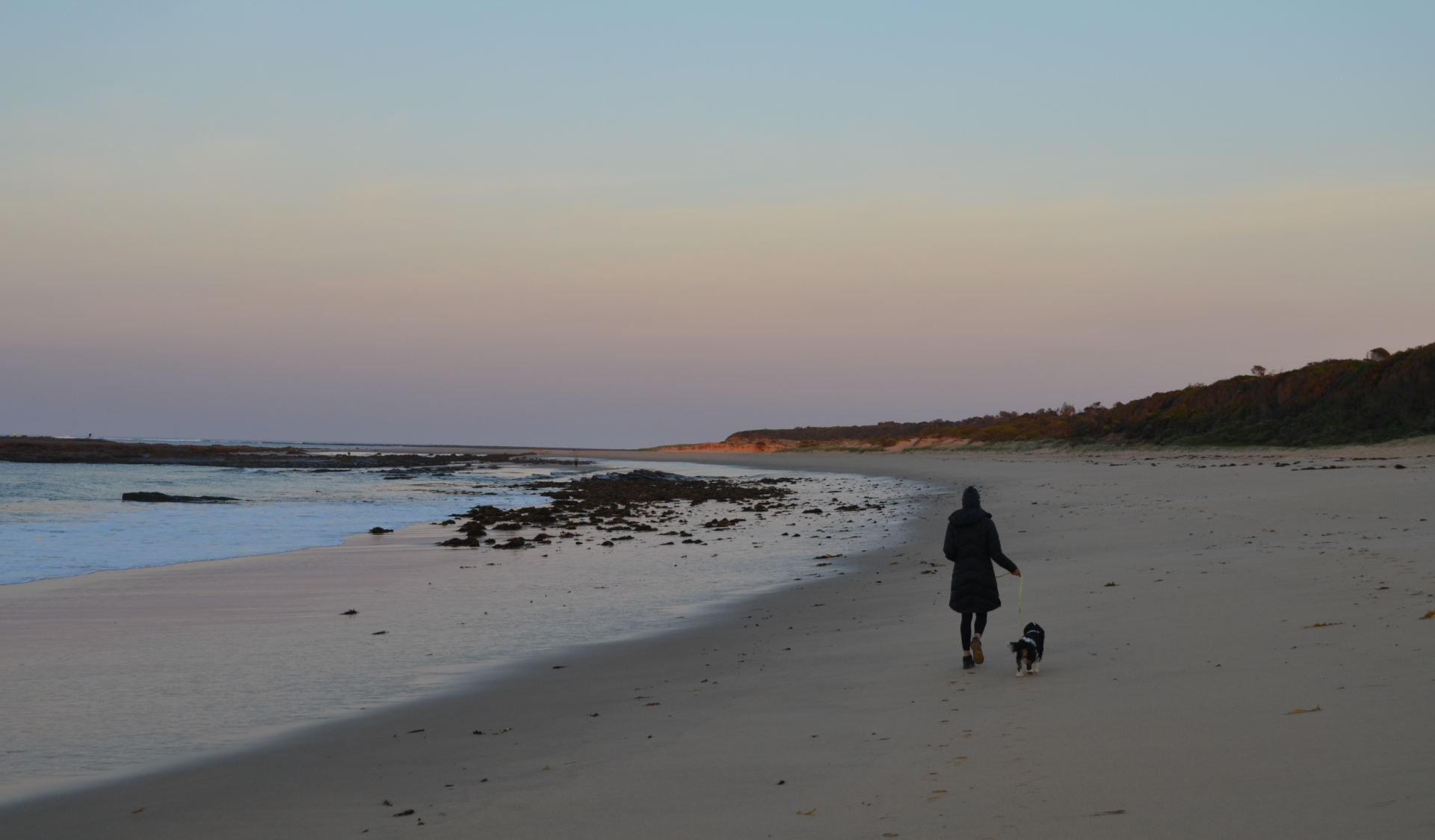 A woman walking her dog along the beach at Undertow Bay in Yallock-Bulluk Marine and Coastal Park