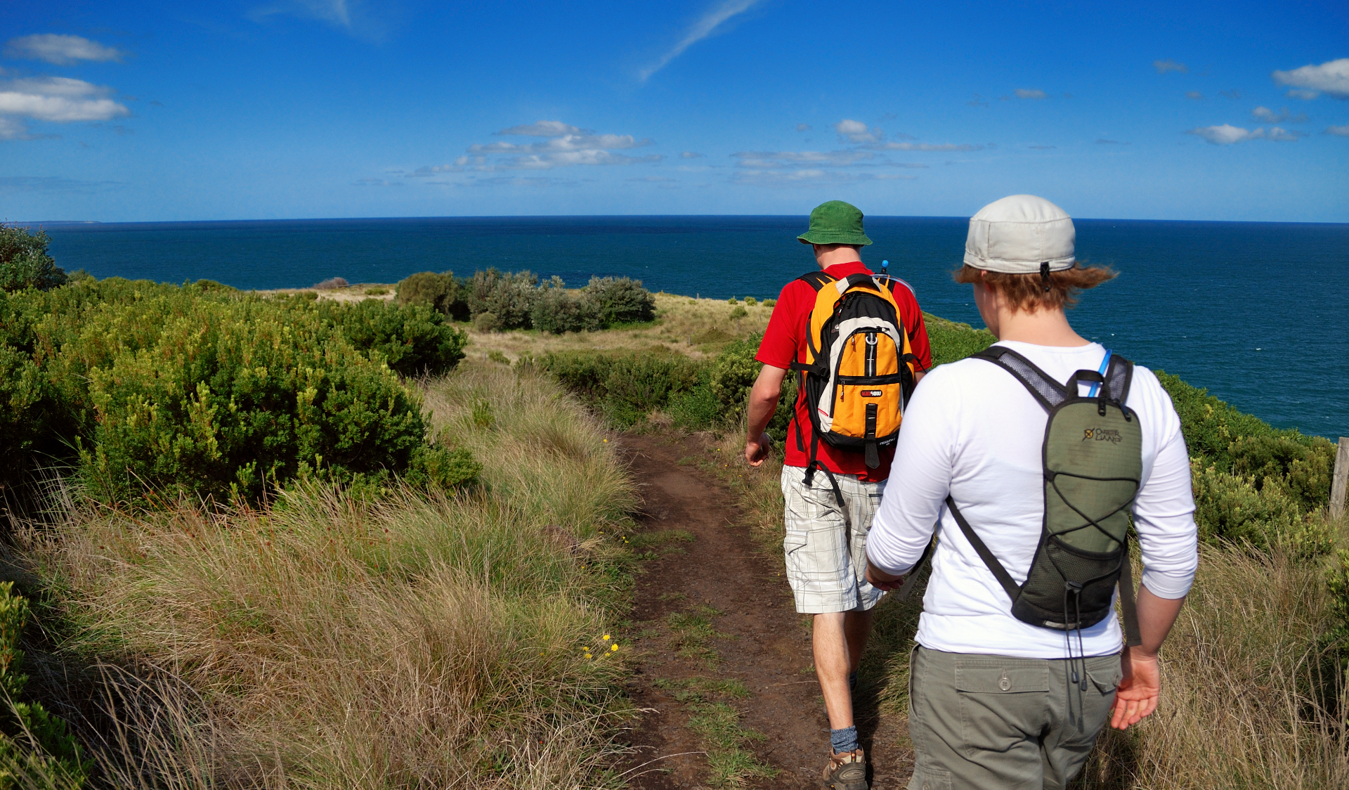 Two men with hats and backpacks walk along the George Bass Coastal Walk