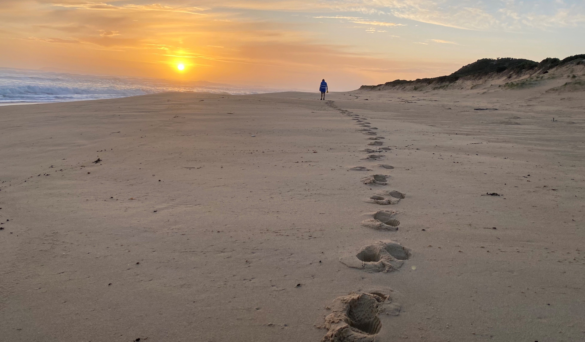 A man walks along Willimsons Beach with footprints behind at sunset