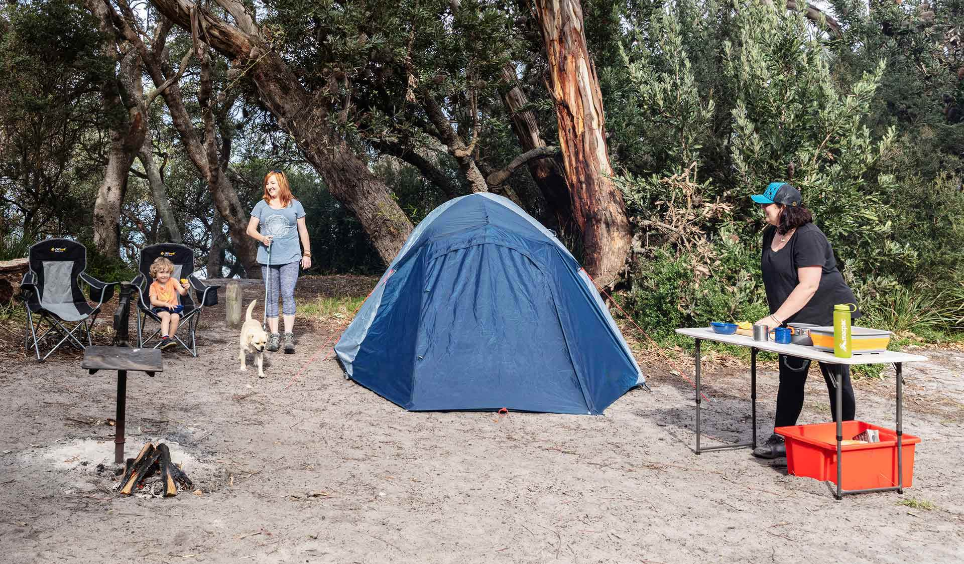 A women walks her dog into the campsite while another women prepares food as her son looks on.
