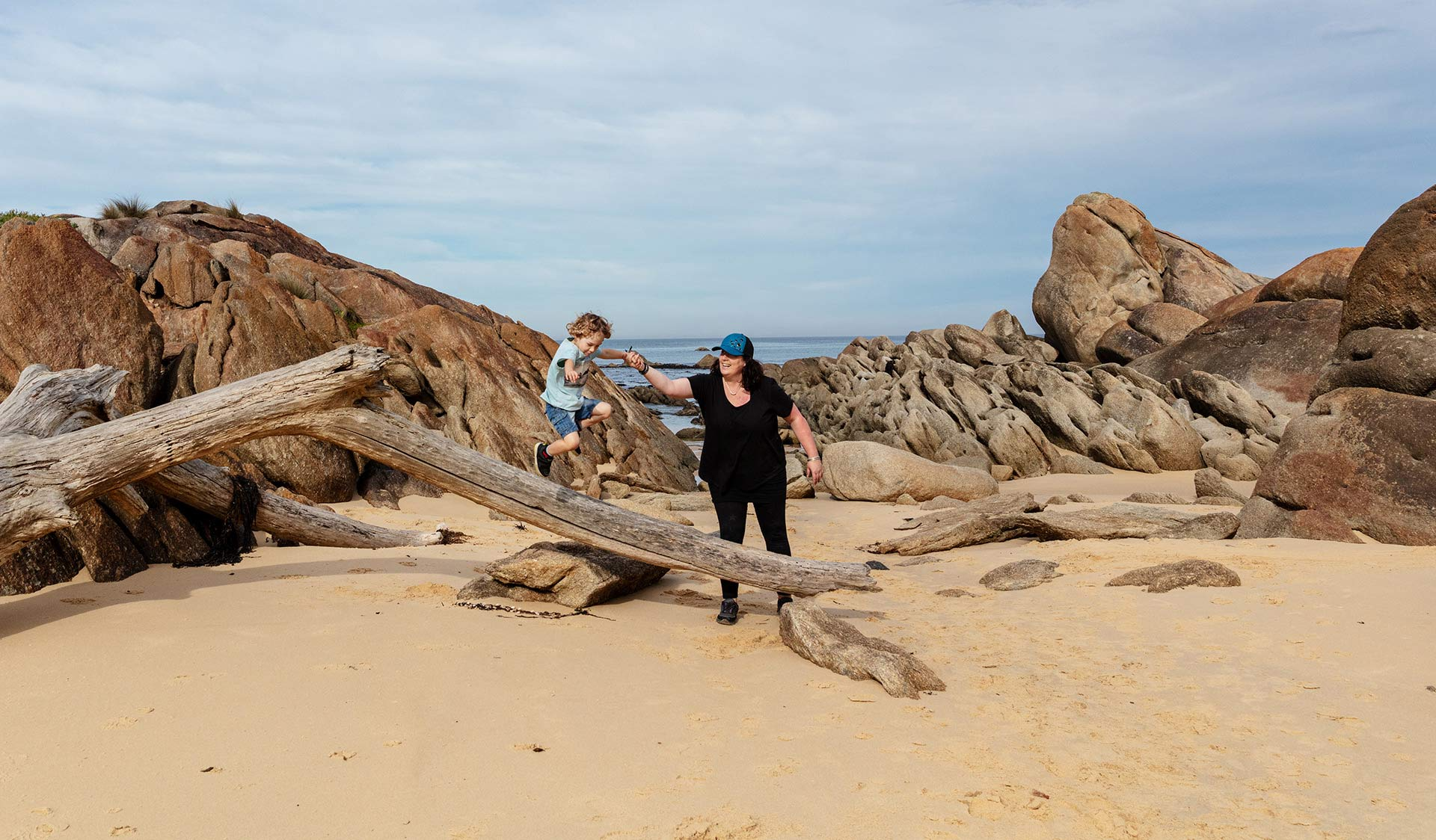 Mum helps her young son as he jumps off a large piece of drift wood at West Cape Beach.