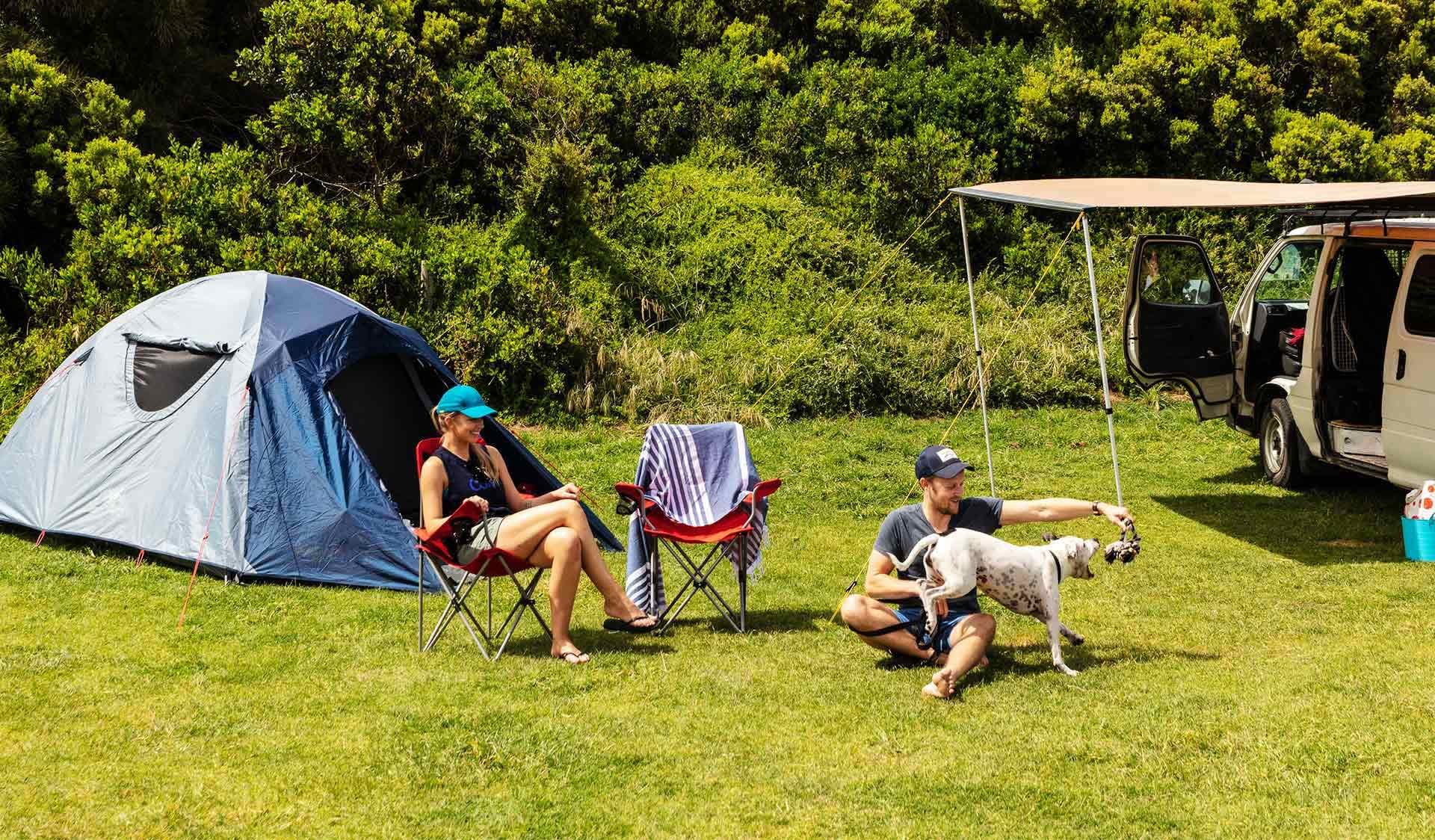 A couple in their thirties play with their dog at Johanna Beach Campground next to their tent and campervan.