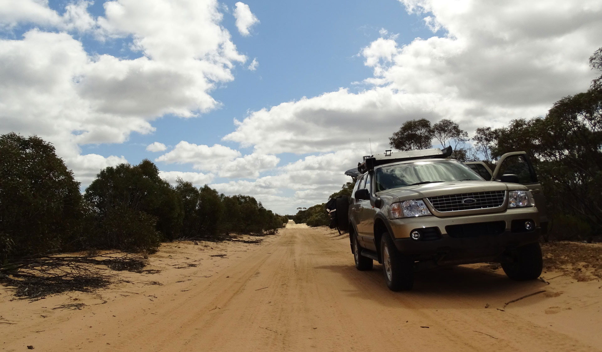 A four wheel drive is parked to the side of a a sandy track at Wyperfeld National Park with a cloudy sky overhead.