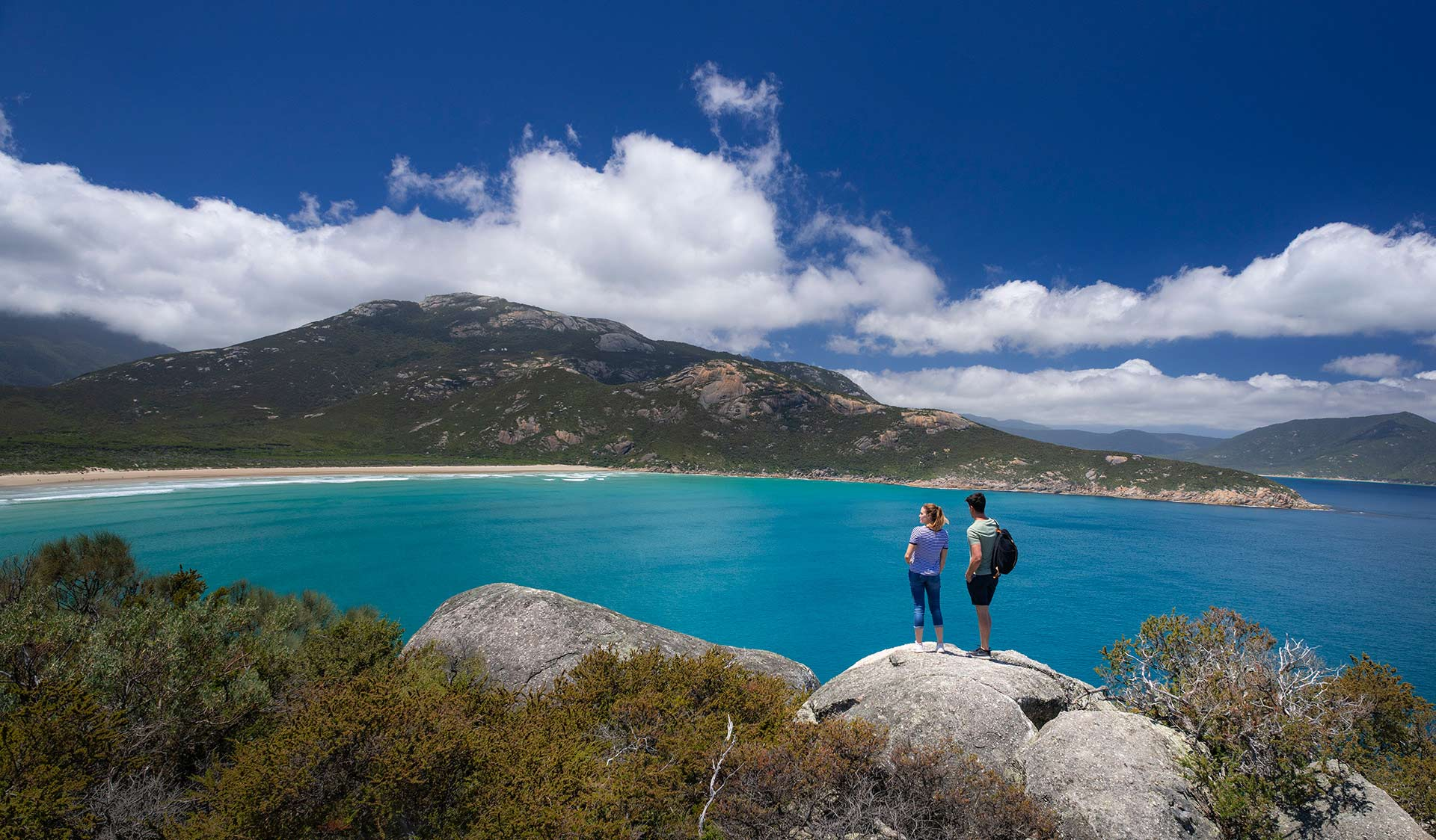 A couple look out over a bay and towards a remote beach on Wilsons Promontory.