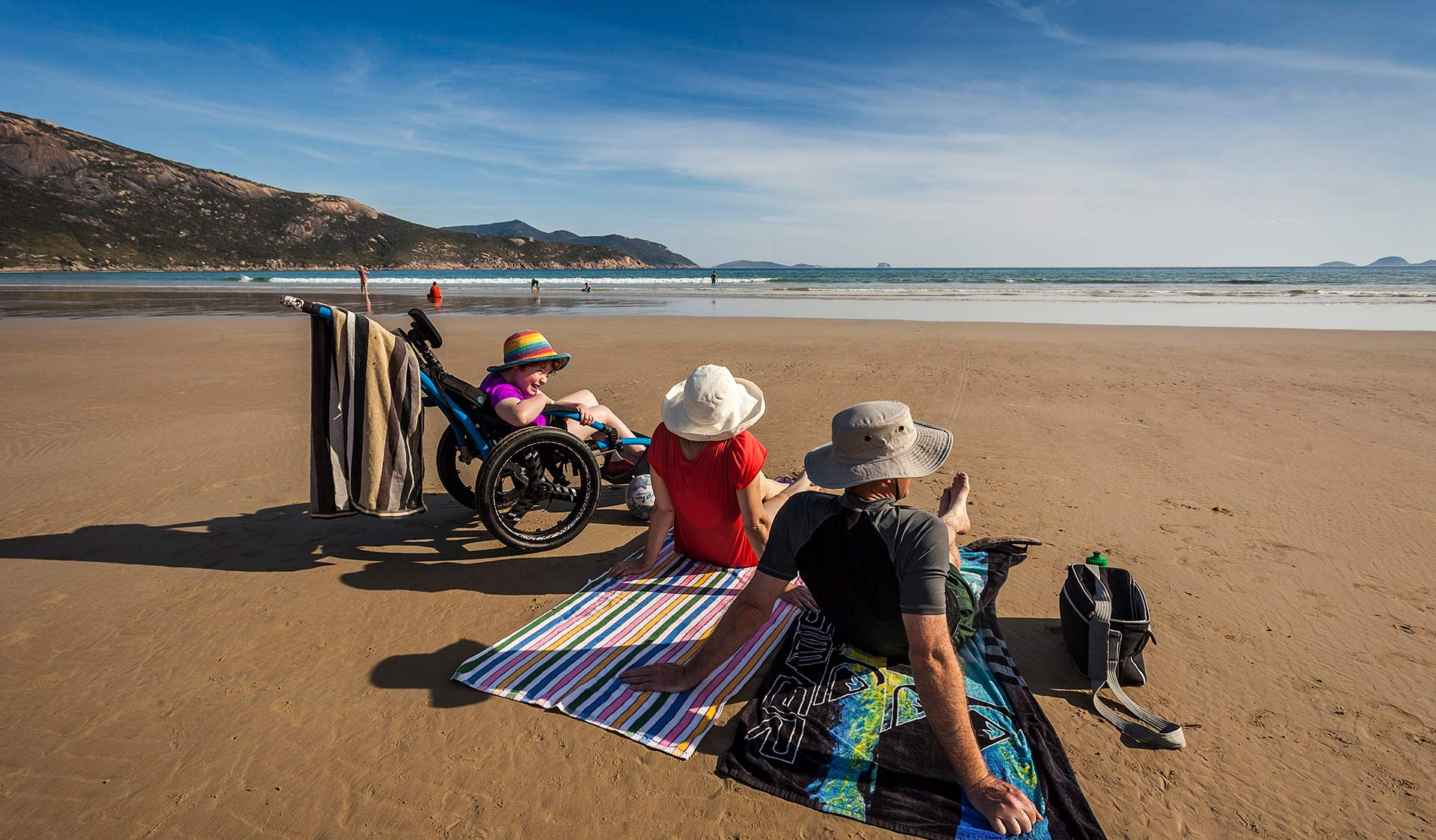 A father and mother sit on Squeaky Beach with their daughter in an all terrain accessibility wheelchair.