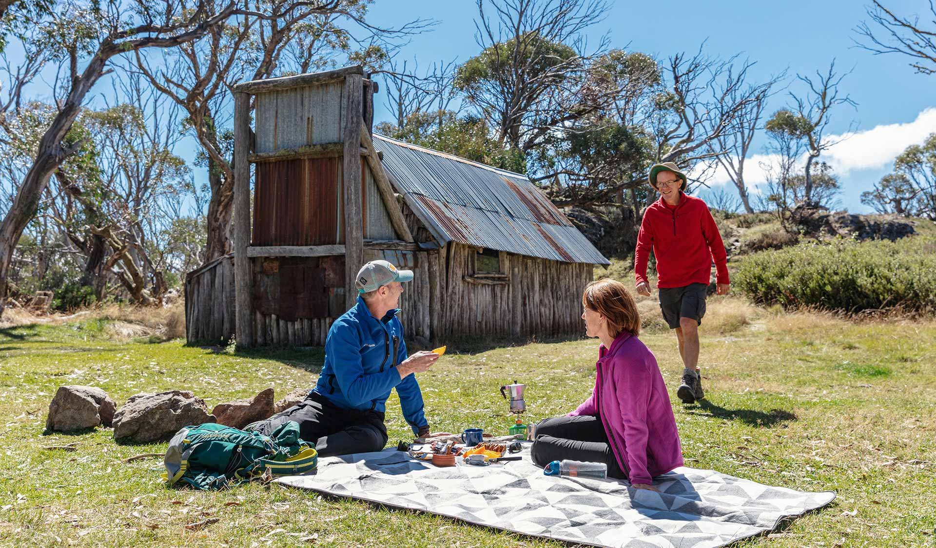 Three friends enjoy a picnic on the grass in front of the historic Wallace Hut.