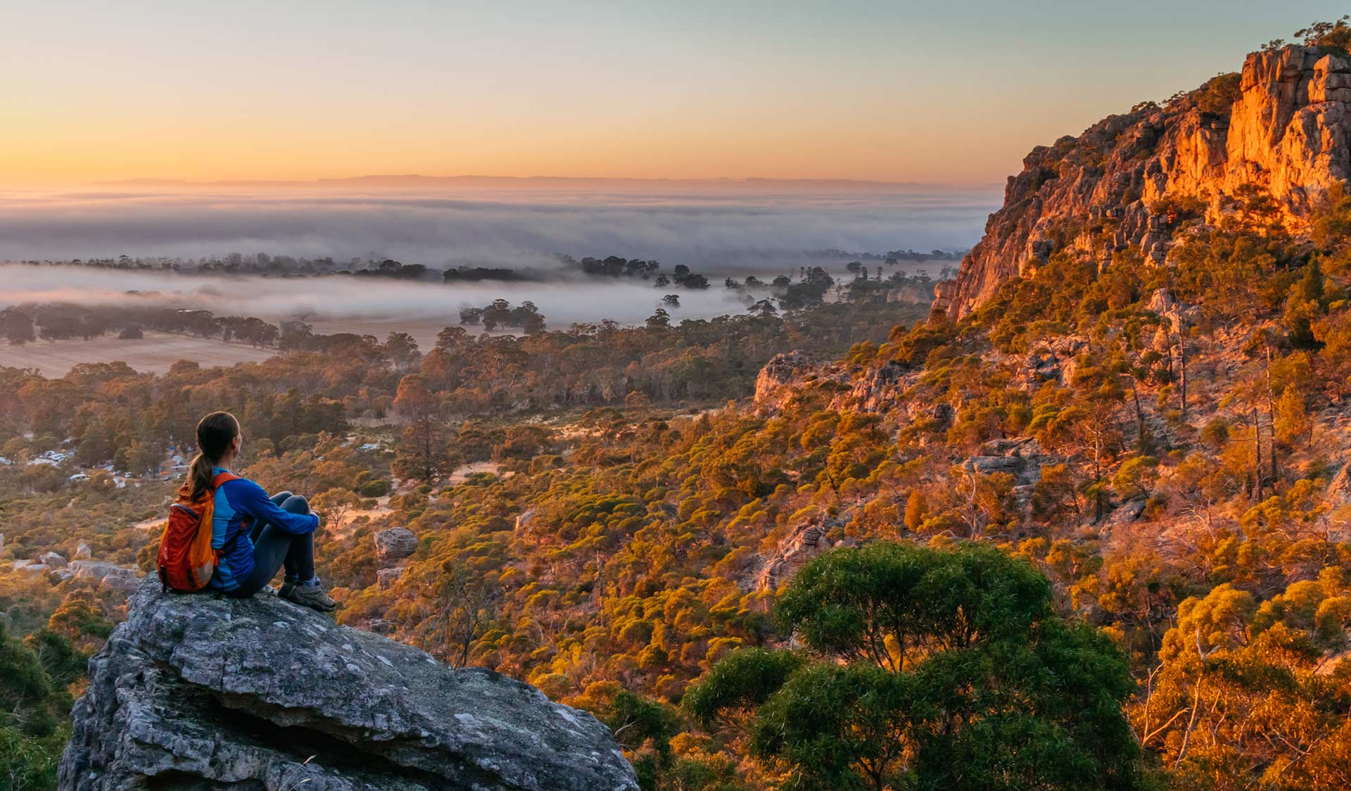 A walker stops to take in the sunrise at Mt Arapiles.