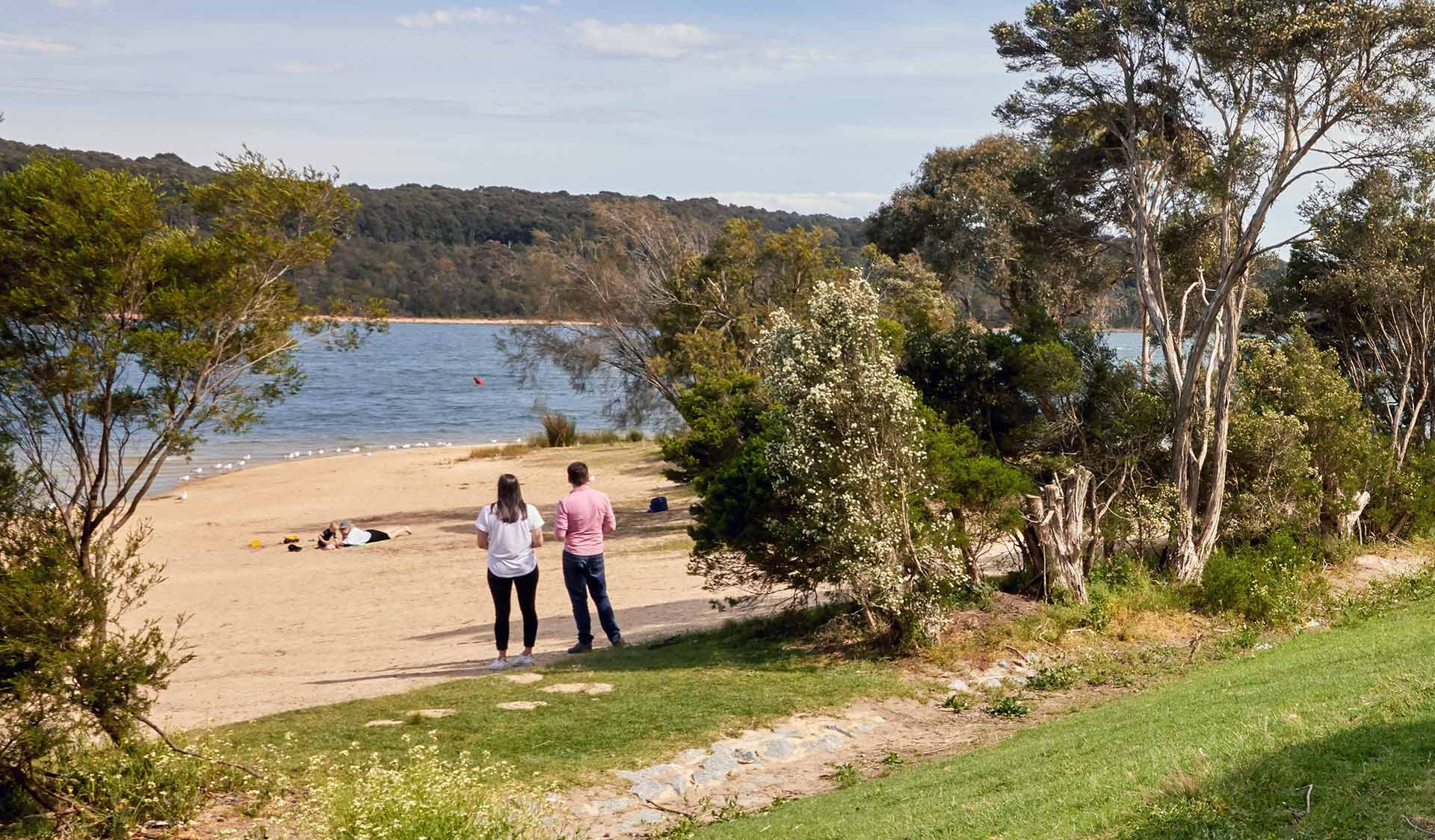 A couple look out over the water from the beach at Lysterfield Lake.