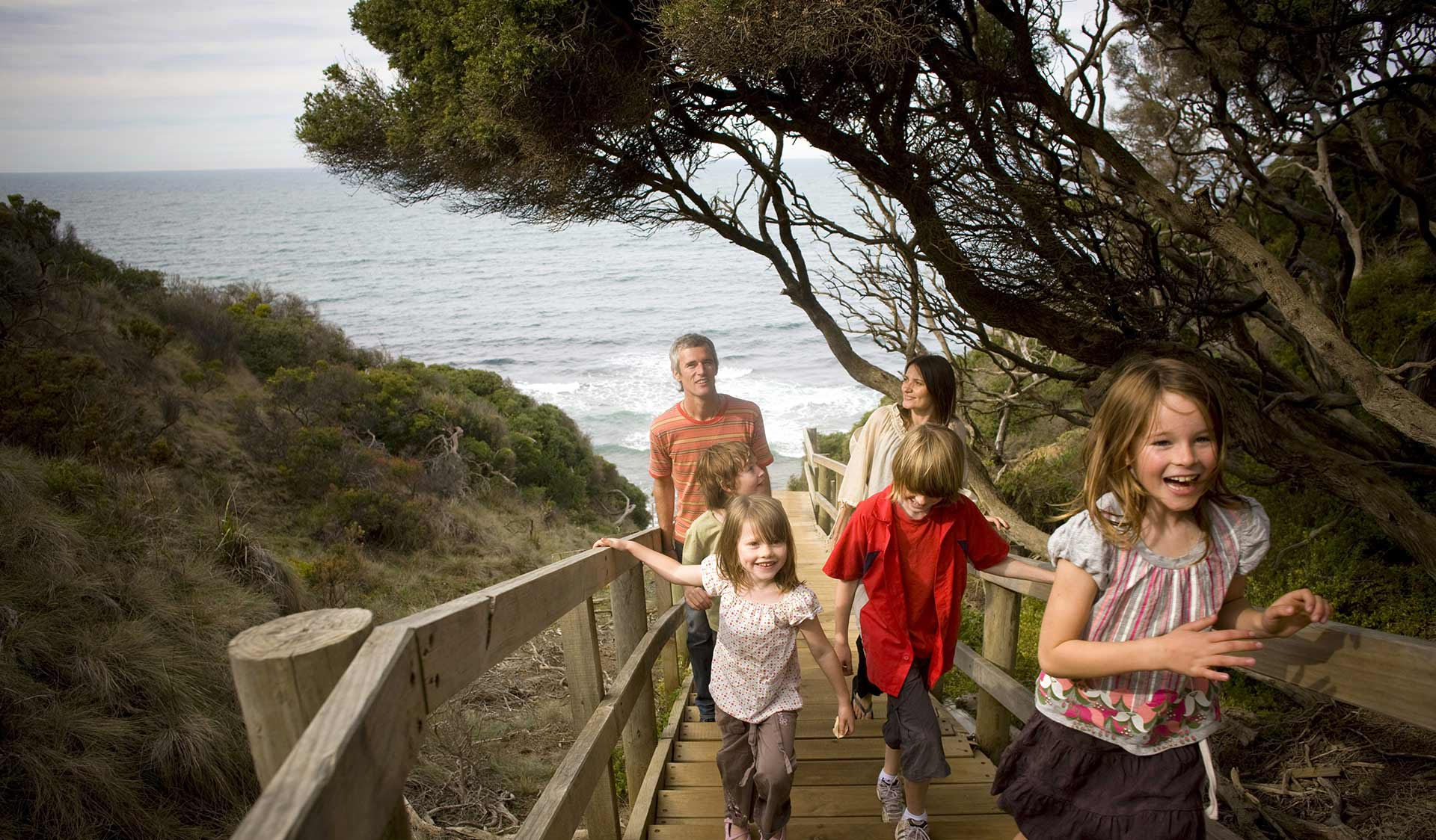 A family walks up a set of wooden stairs on the Surf Coast Walk.