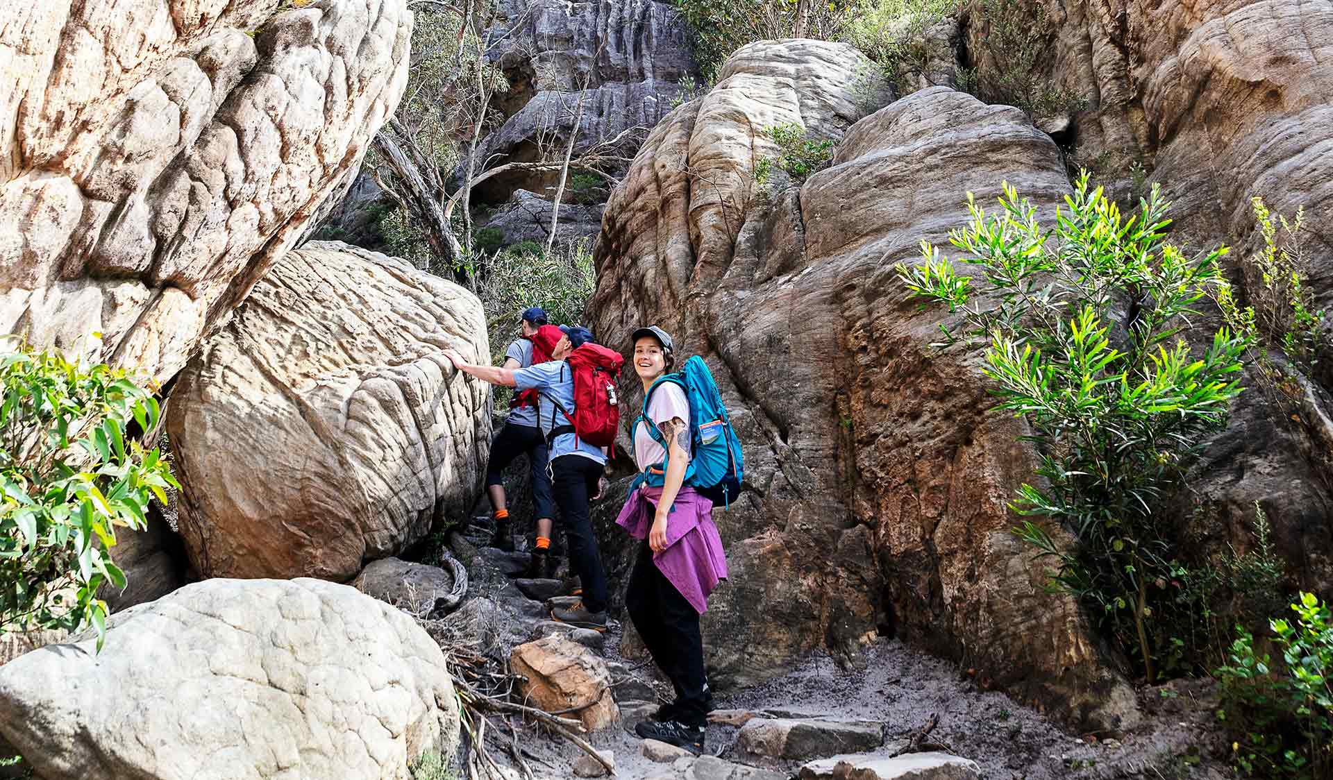 A group of three friends walk through the rocky ravines of the Northern Grampians.