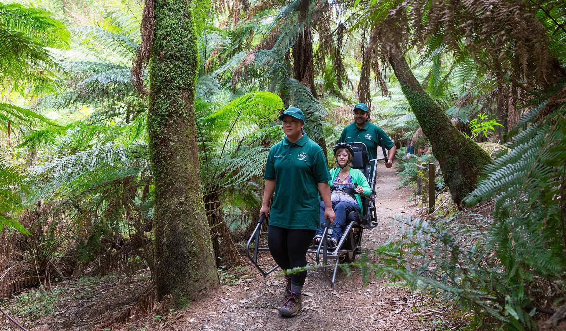 Two people assist a third person in an all terrain wheelchair along a track surrounded by nature