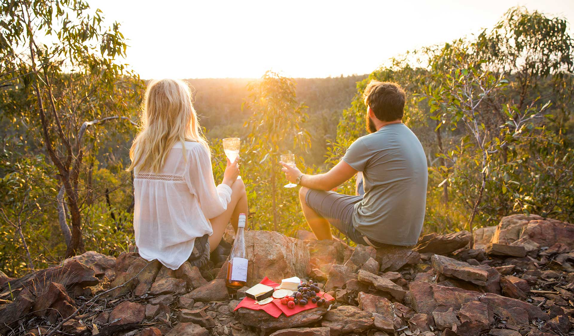 A couple enjoy a sunset picnic in the Brisbane Ranges National Park.