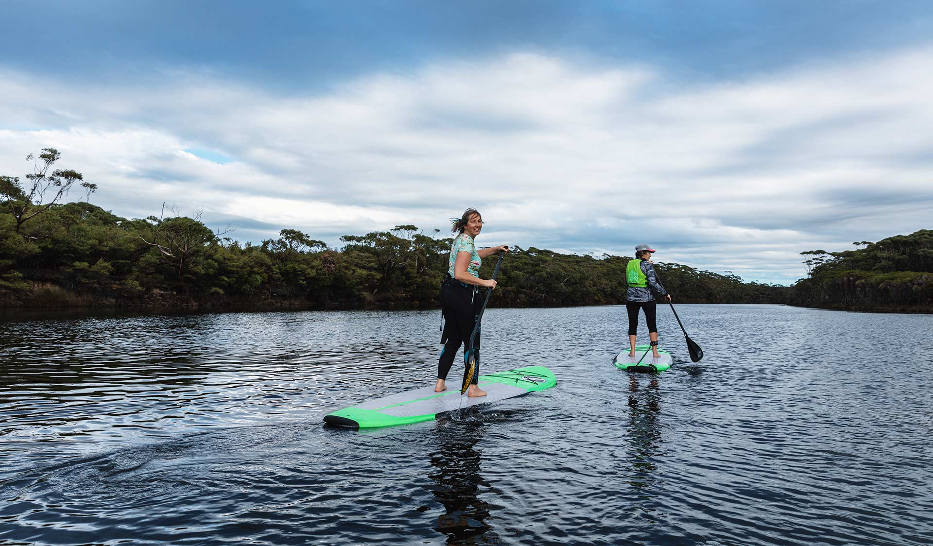 Two women stand-up paddle boarders paddle up the Yeerung River.