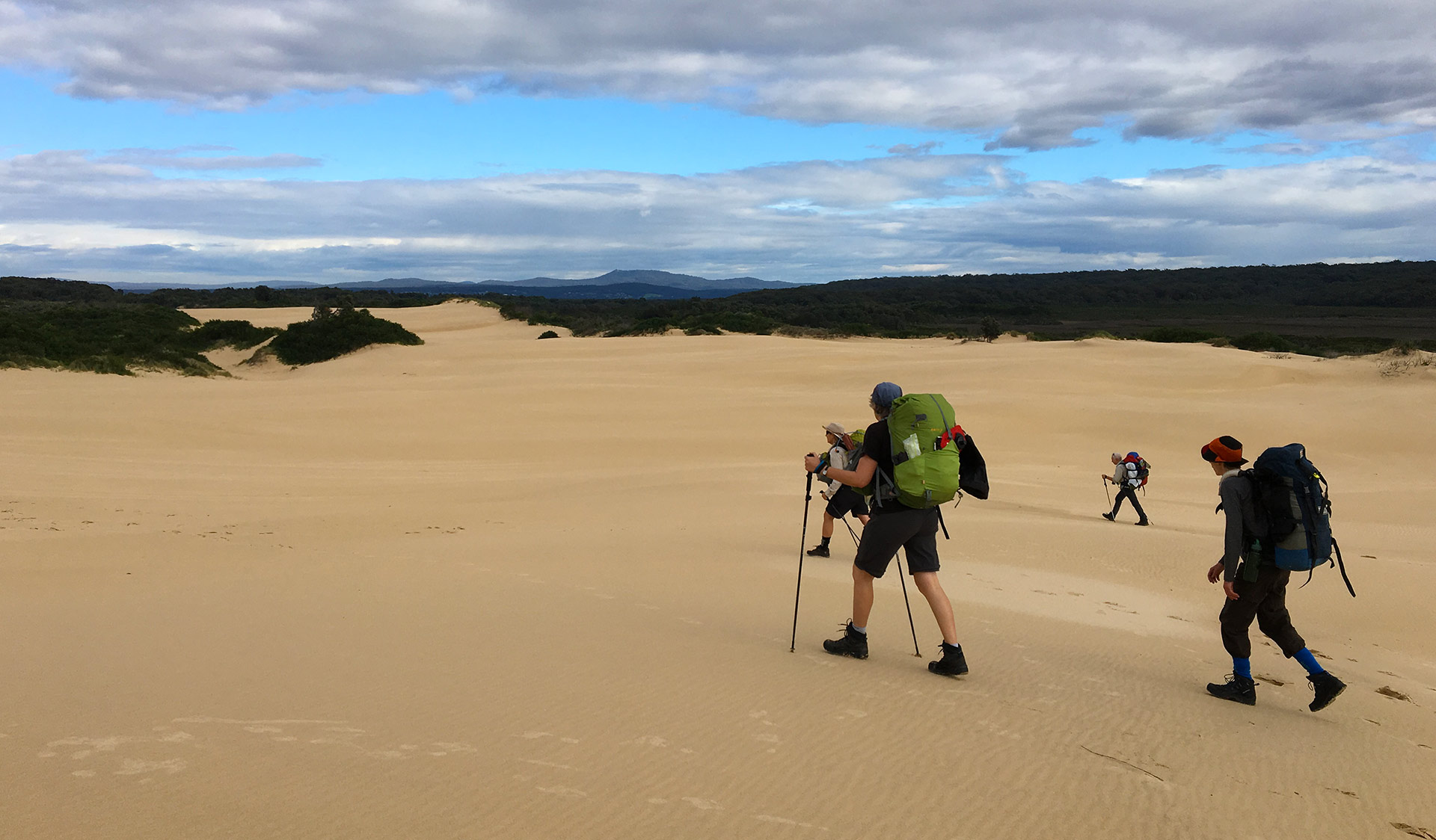 Four friends walk across the sand dunes along the Wildernous Coast Walk close to Mallacoota Inlet.