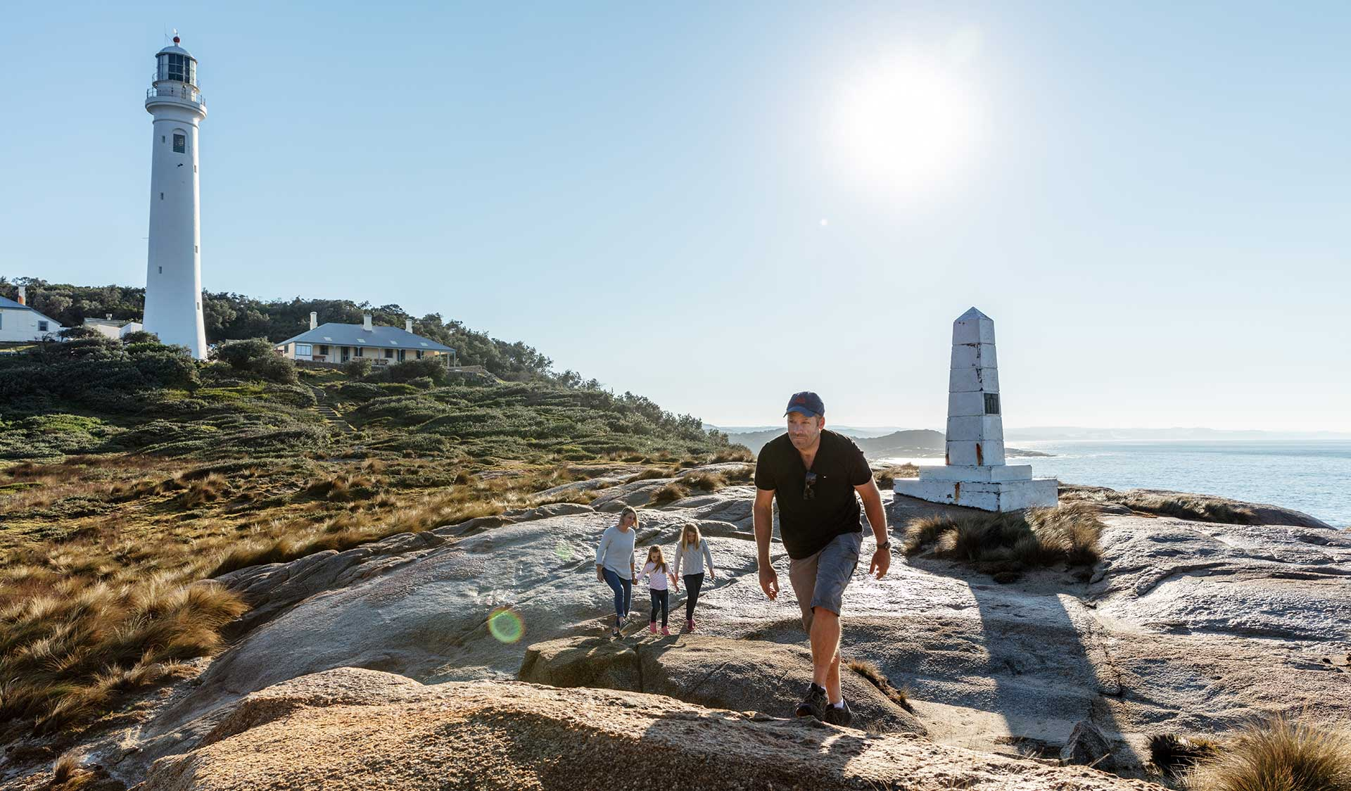 A father leads his family across the rocks in front of the Point Hicks Lighthouse and cottage.