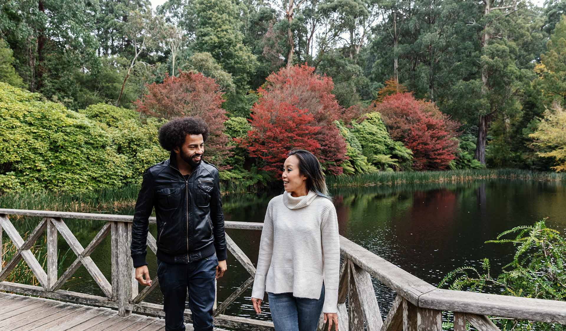 A man with an afro wearing a leather jacket and woman wearing a cream knitted jumper turn and walk away from a lake in the Dandenong Ranges Botanical Gardens.