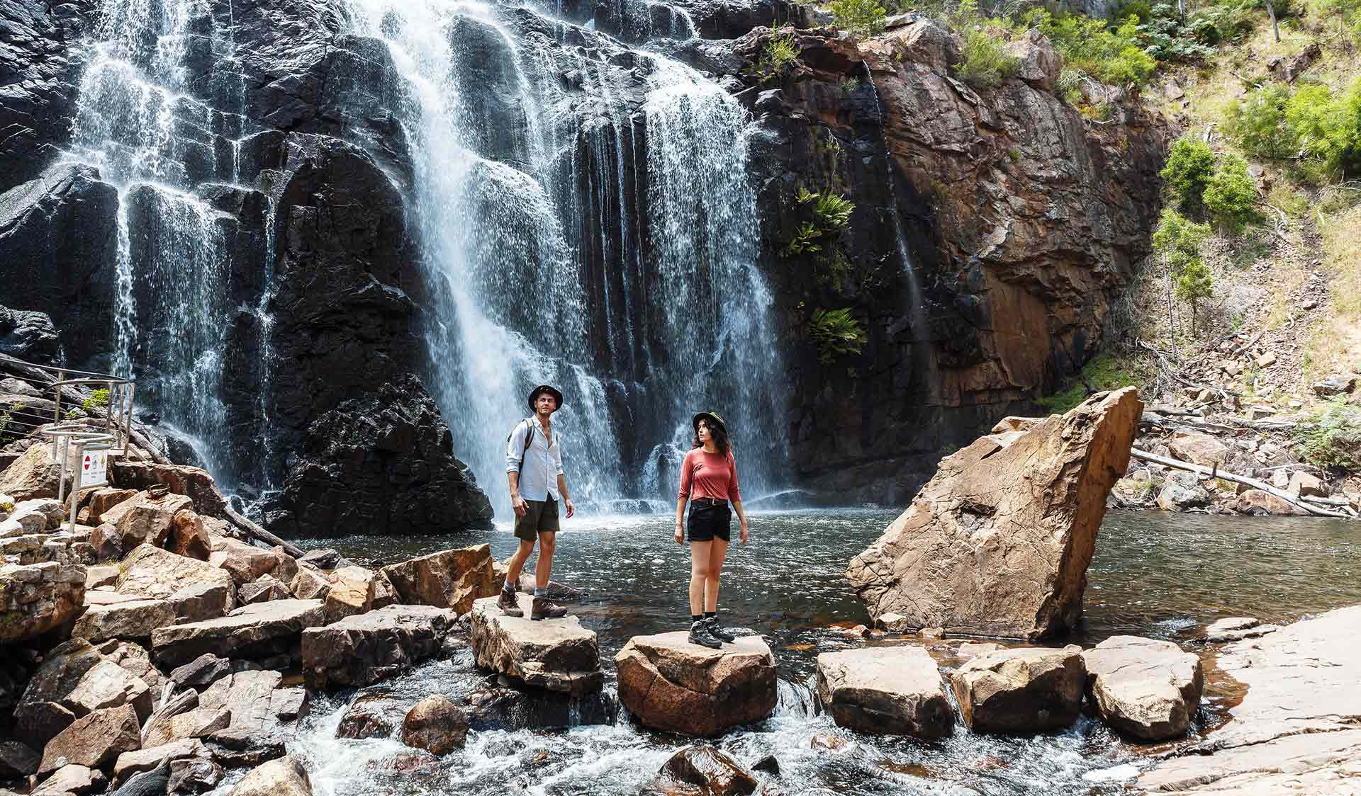 A young couple cross the stream on rocks in front a the spectacular MacKenzies Falls.