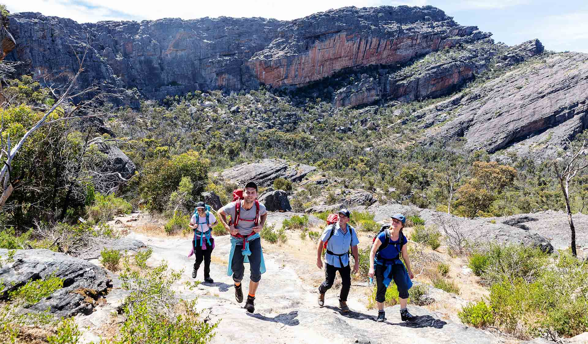 Four friends looking up at the surrounding scenery during their hike at Mount Stapylton