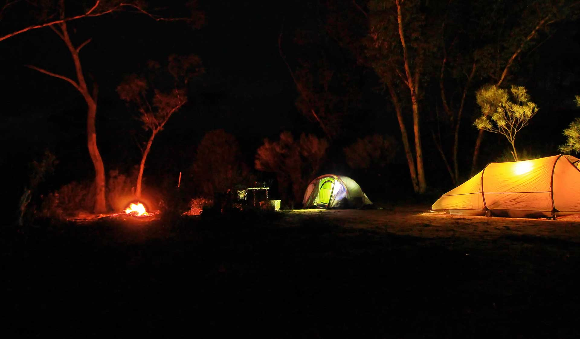 Three tents and a campfire at night time.