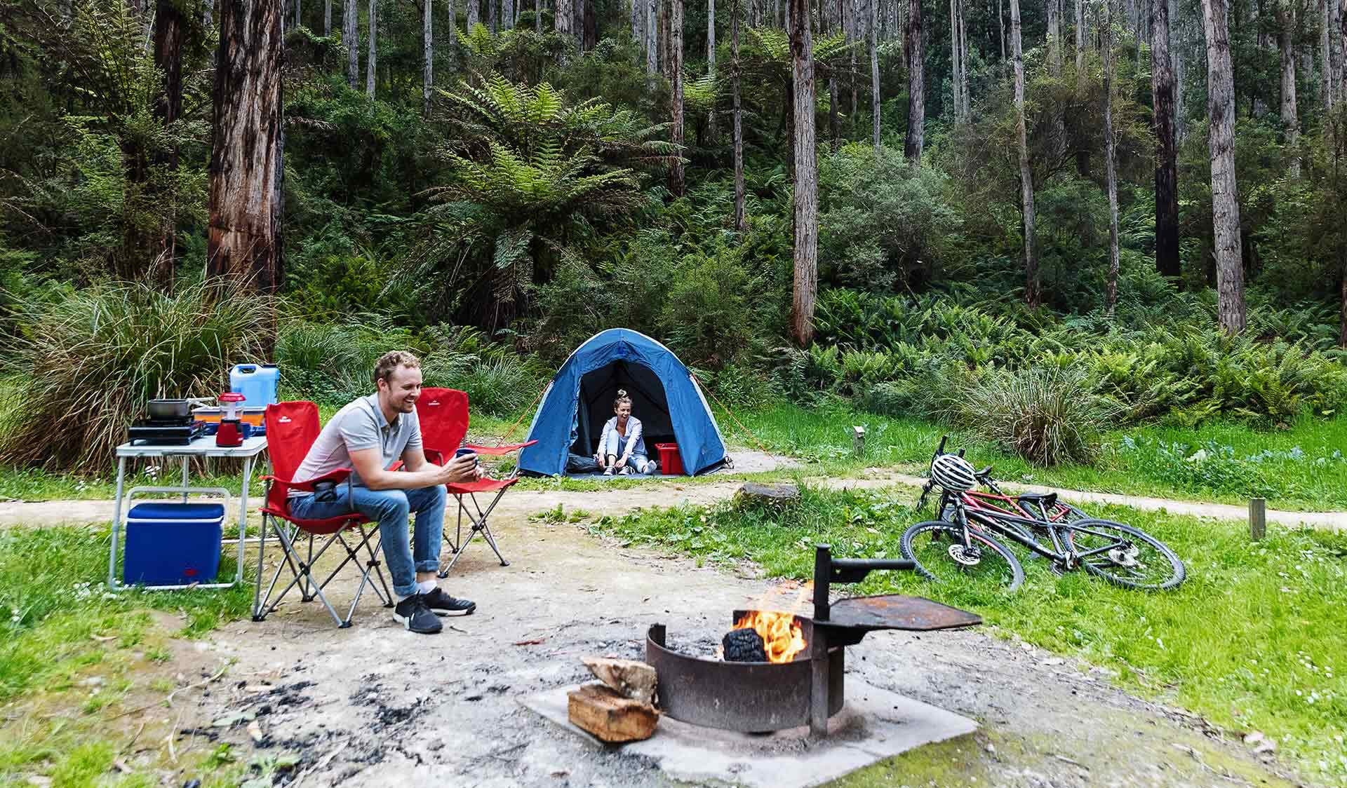 A couple in their later twenties enjoy a joke while at their campsite at Lake Elizabeth Campground in the Great Otway National Park.