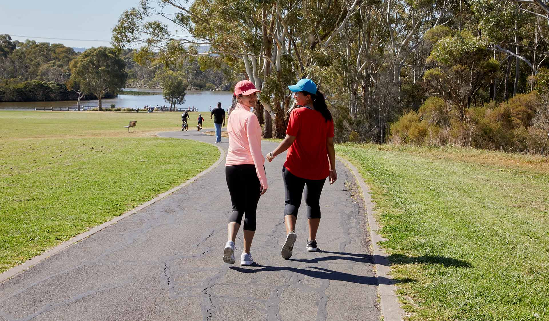 Two women in activewear walking around the lake for exercise