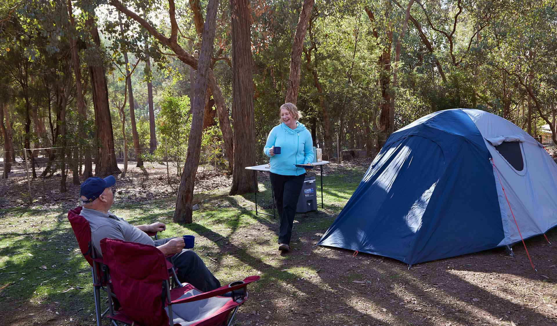 A couple prepare a meal at their camp ground at Lakeside in Fraser Camping Area in the Lake Eildon National Park.