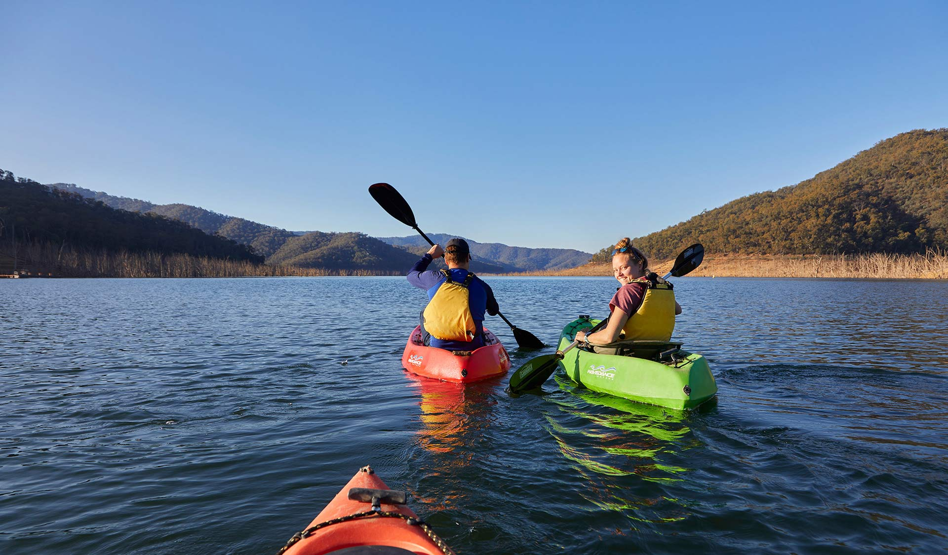 A young couple paddle kayaks on a sunny afternoon across Lake Eildon.