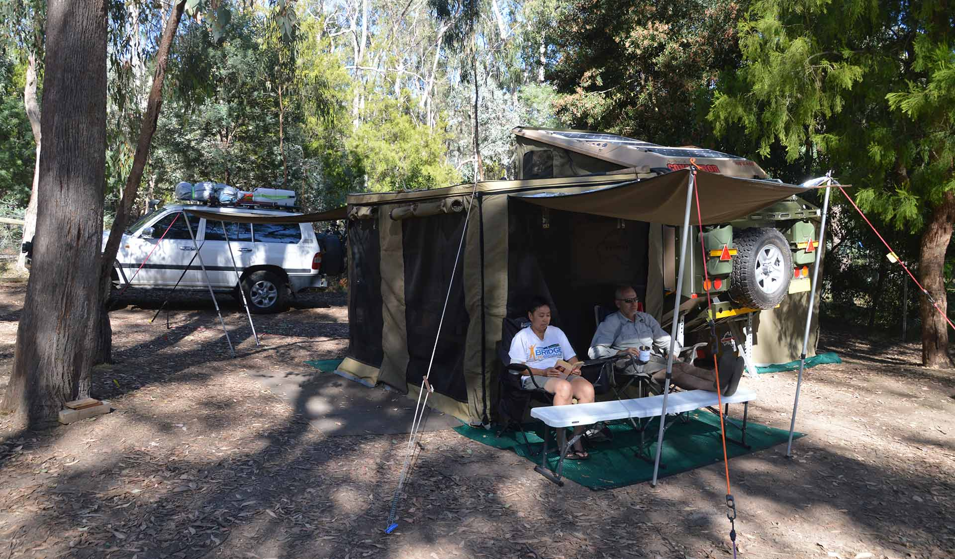 Two friends relax under the shelter of their camper trailer at Fraser Camping Area in the Lake Eildon National Park.