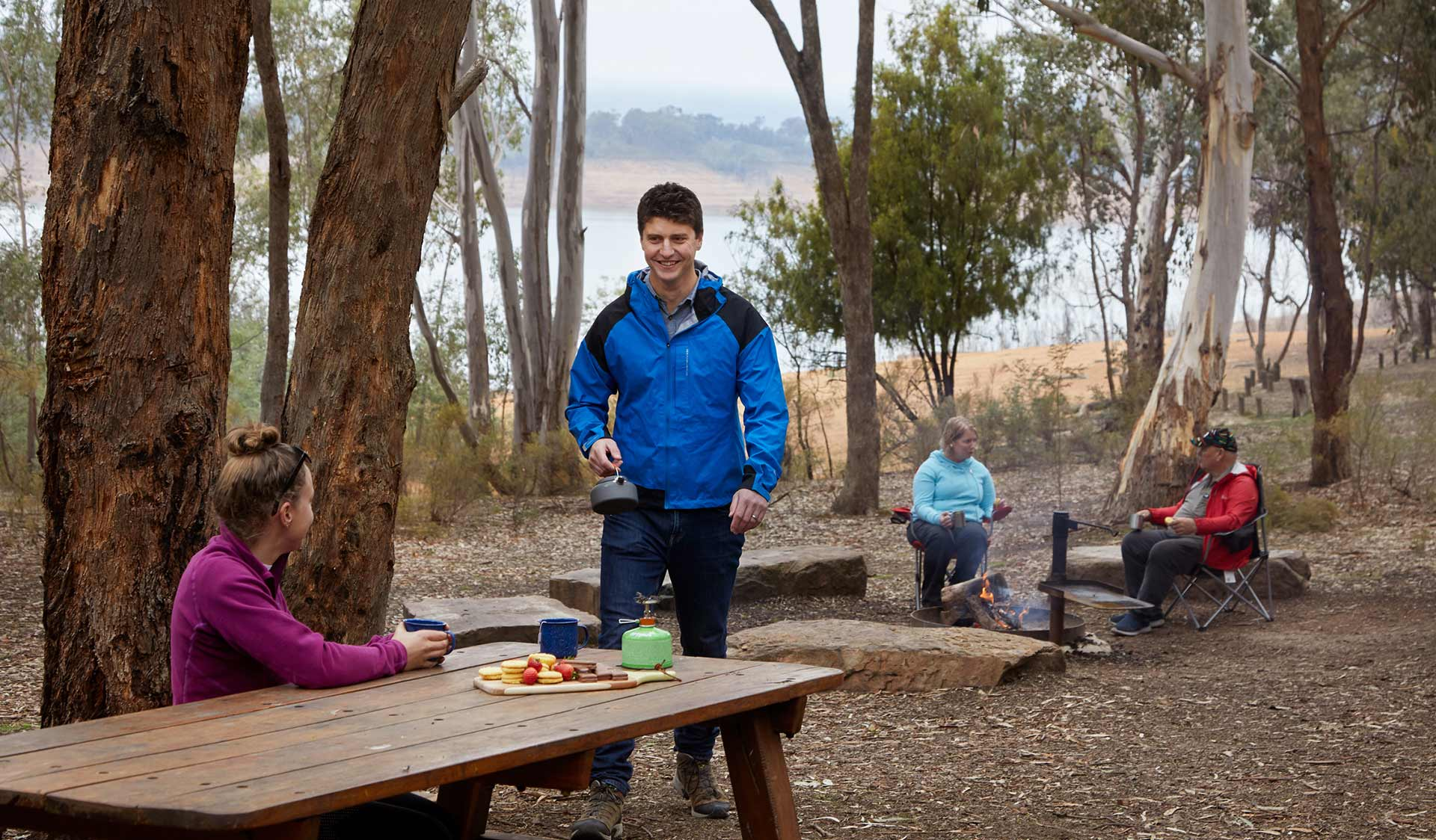 A man brings a kettle to the picnic table where his partner is sitting, while an older couple sit around a campfire in the background.