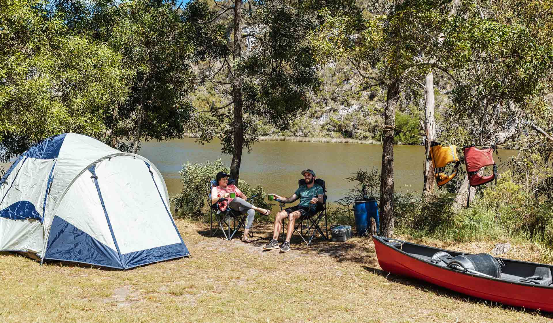 Two campers relax at their campsite after a long paddle.