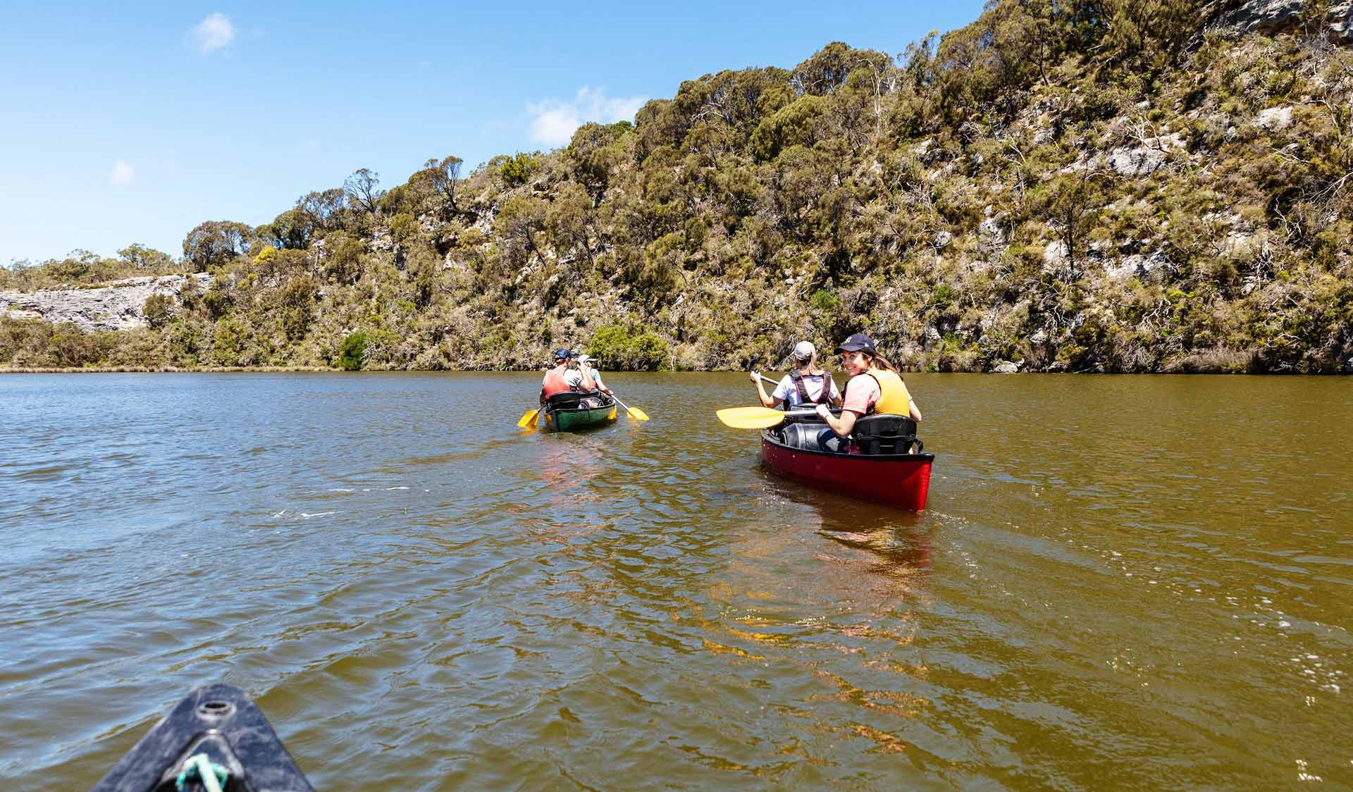 Two canoes float down the Glenelg River on a camping trip.