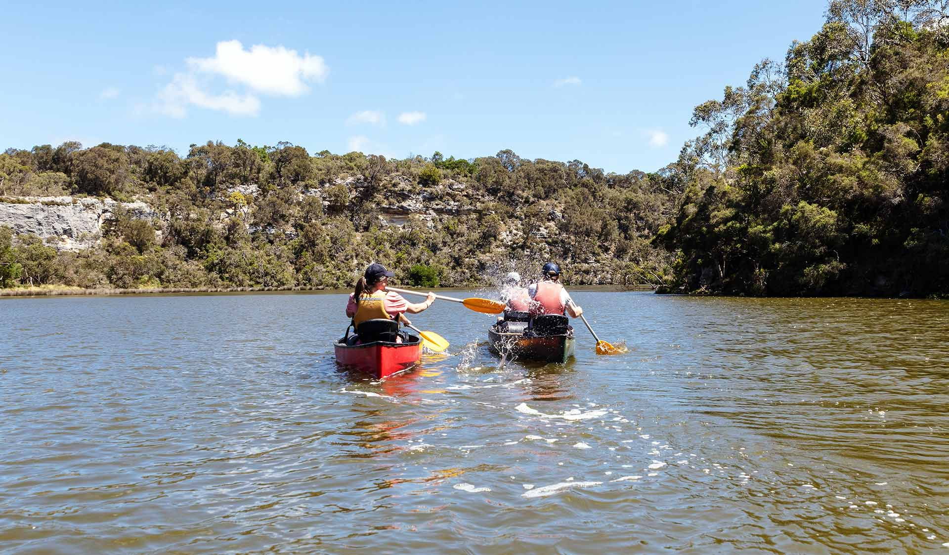 A woman playfully splashing a friend in another canoe with her paddle on the Glenelg River