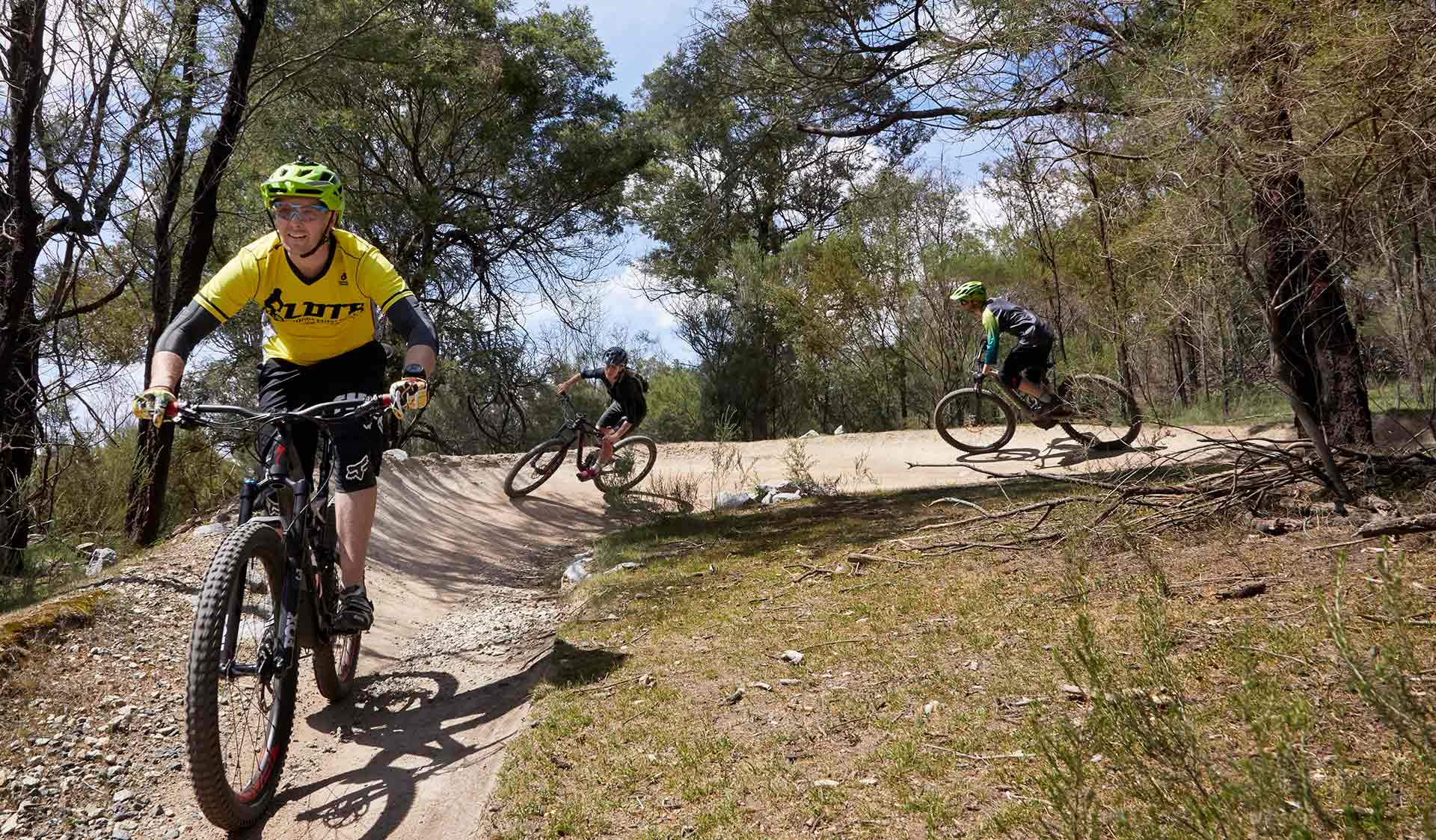 Three mountain bikers turn left through a berm.