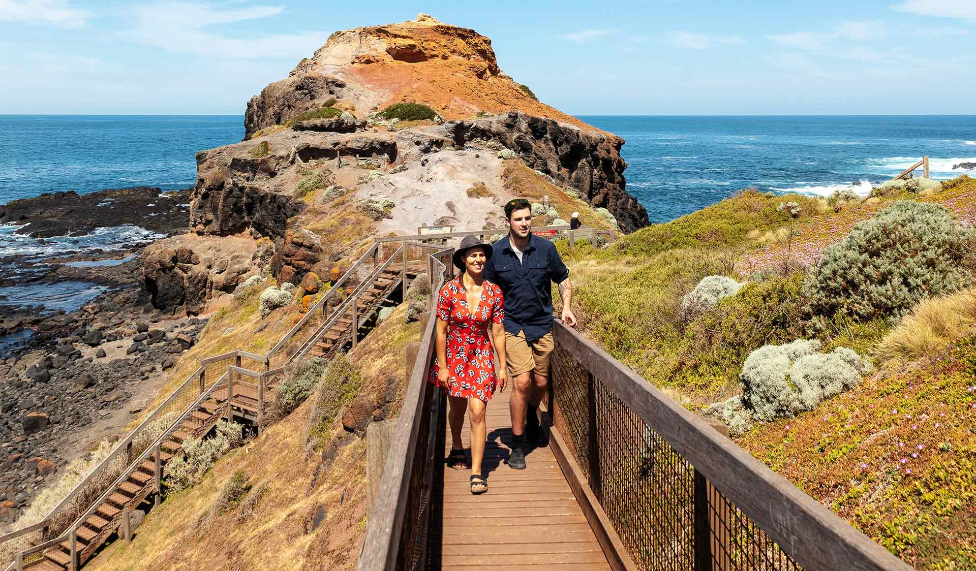 A young couple walk along the board walk at Cape Schank.