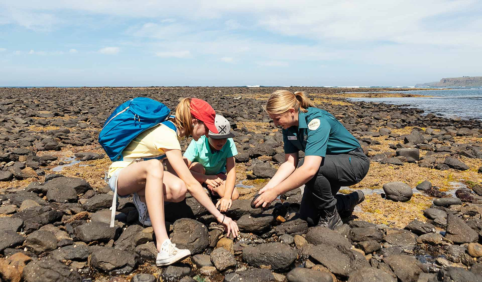 A young boy and girl looking at the marine life with a Parks Victoria ranger at Mushroom Reef