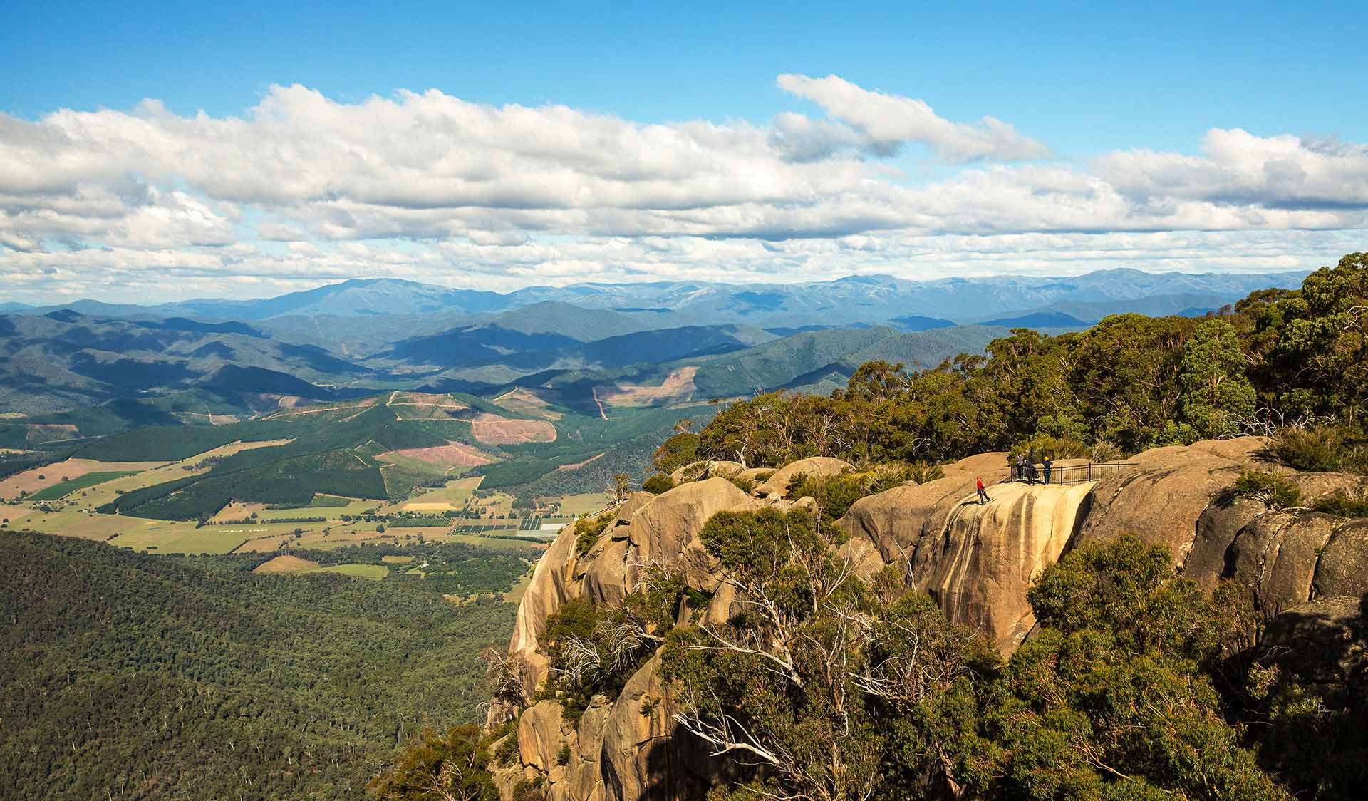 A group of abseilers descend into the Gorge at Mt Buffalo with views of the Bogong High Plains in the back ground.
