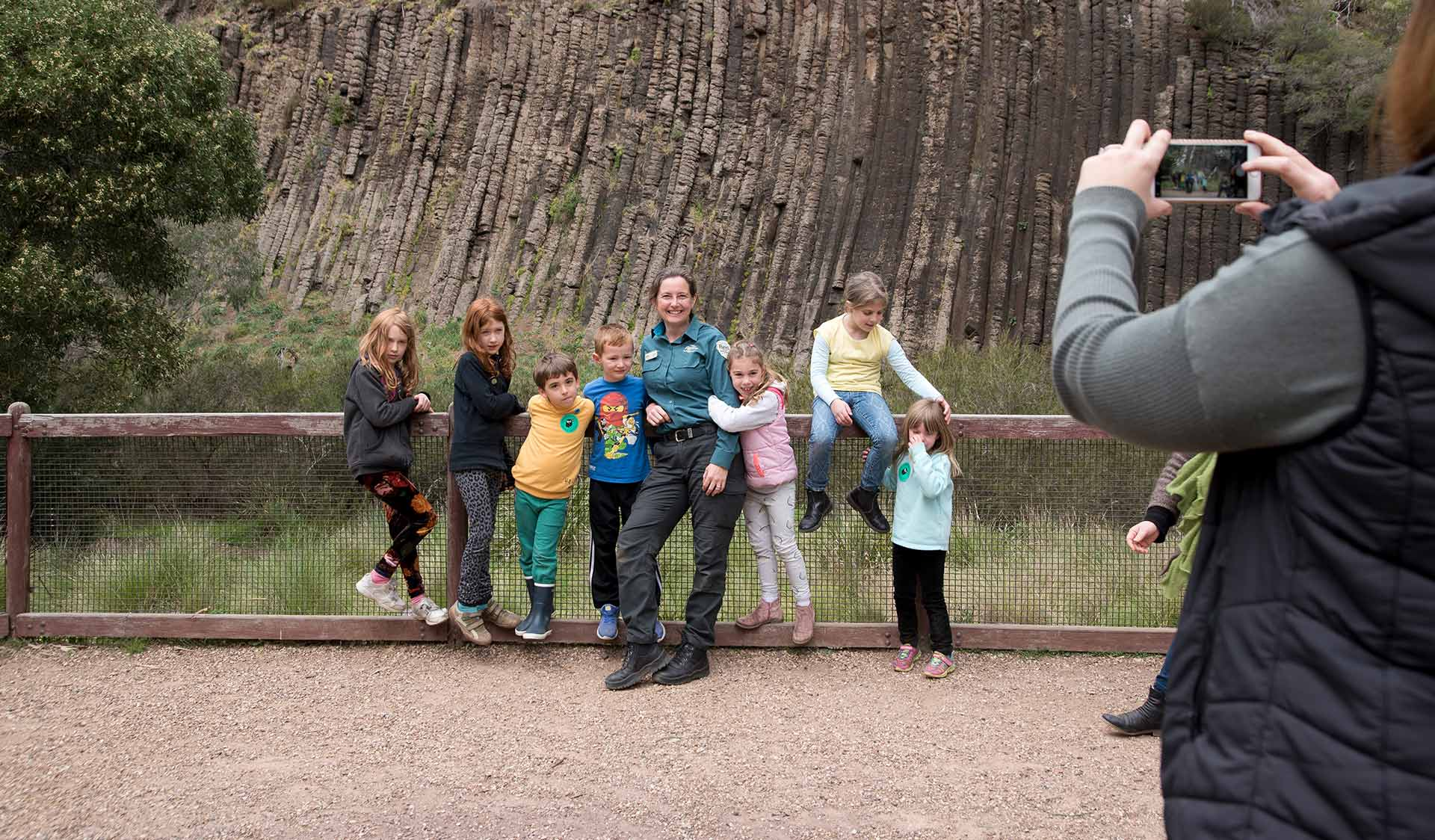 A Parks Victoria Ranger poses for a photograph with 7 young children in the Junior Rangers Program in front of the rock formation at Organ Pipes National Park.
