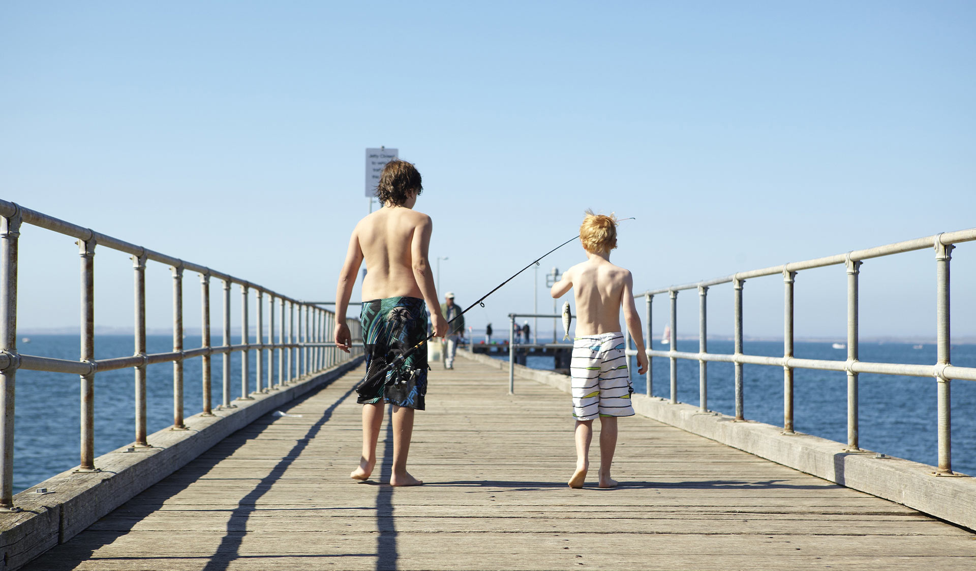 Two children holding fishing rods walk along Flinders Jetty.