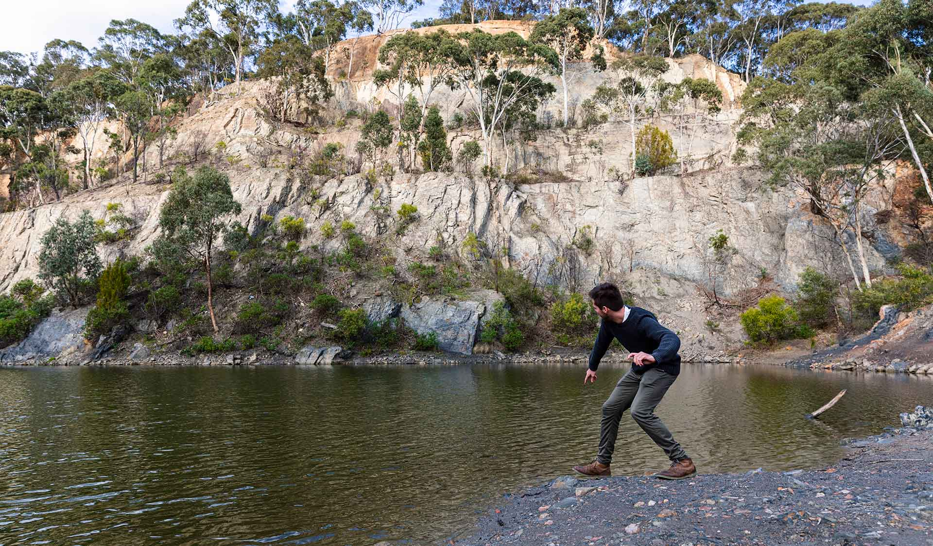 A man skims a rock along the water at Blue Lake at Plenty Gorge Park
