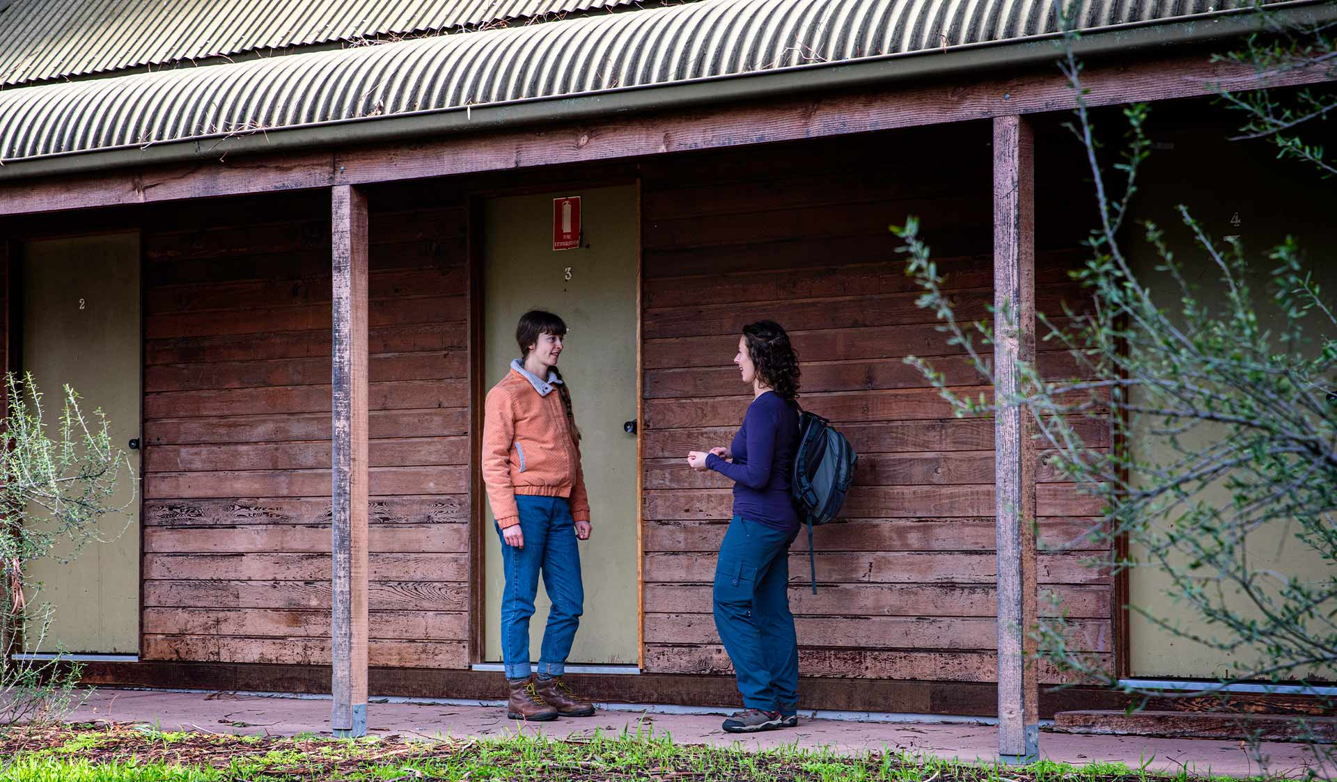 Two women stop for a chat outside the dorm rooms at Nioka Bush Camp.