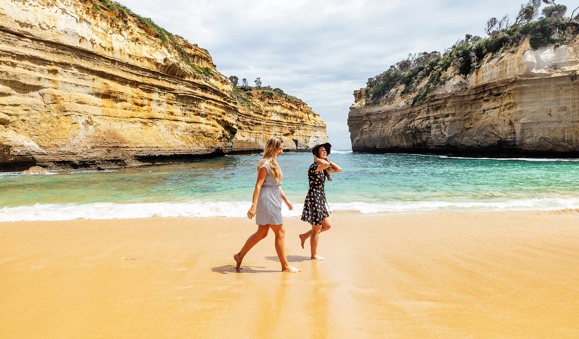 Two young wearing dresses stroll across the beach at Loch Ard Gorge.
