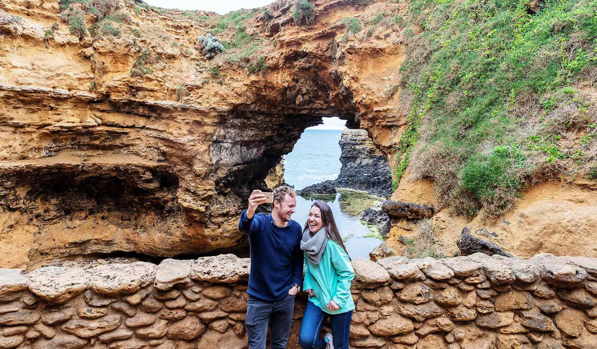 A couple take a selfie in front of the Grotto in Port Campbell National Park.
