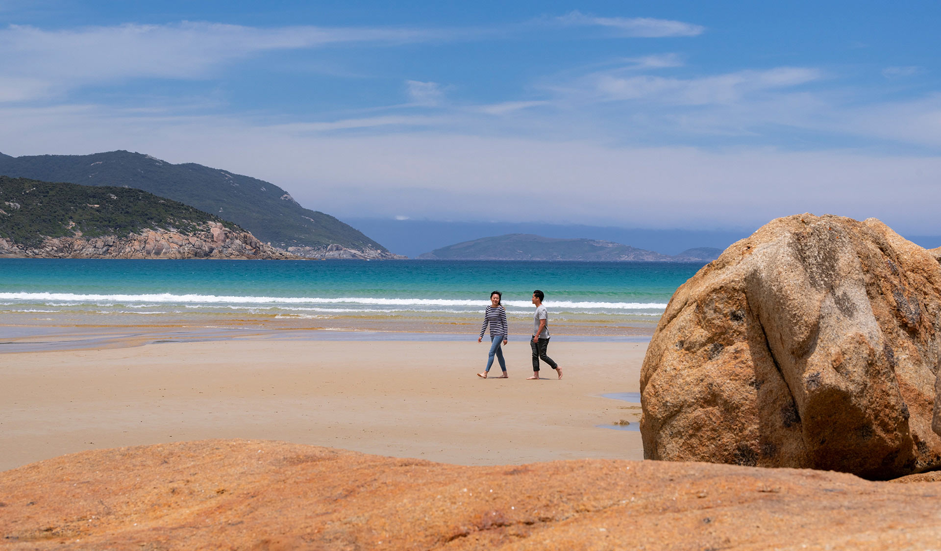 Two people walk along a pristine beach on Wilsons Promontory.