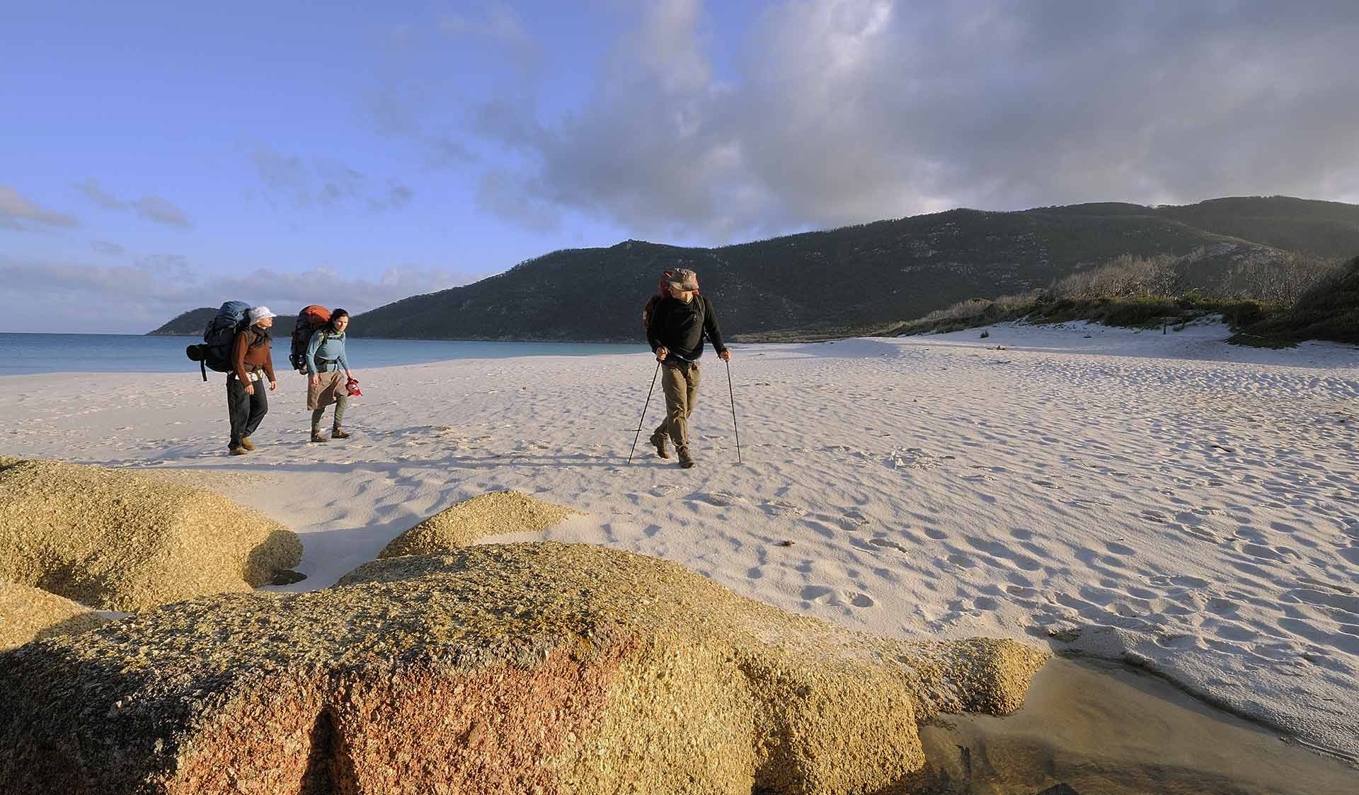 Three hikers walk along the beach at Wilson Promontory National Park.